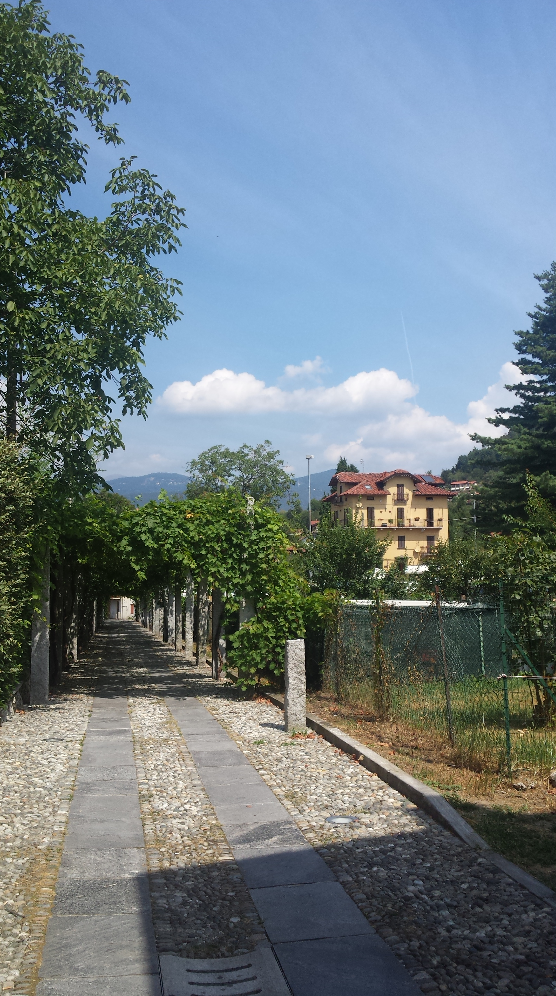 A photo of one of our trips to Italy, a gorgeous yellow house with a red roof stands in front of a mountain range and some blue blue sky. Travel adventures.