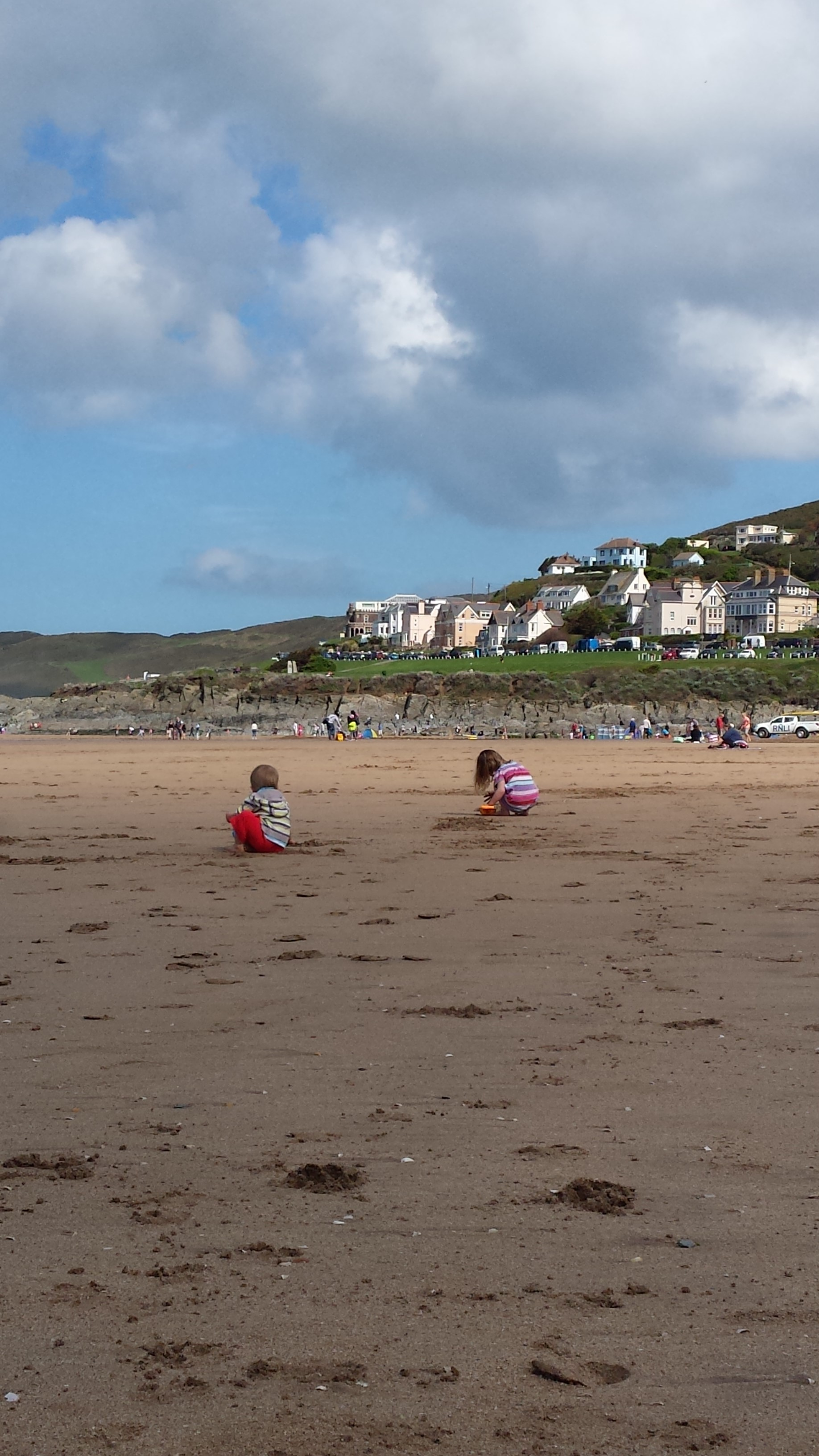 Travel adventures to Woolacombe bay, a view of my children playing on the beach.