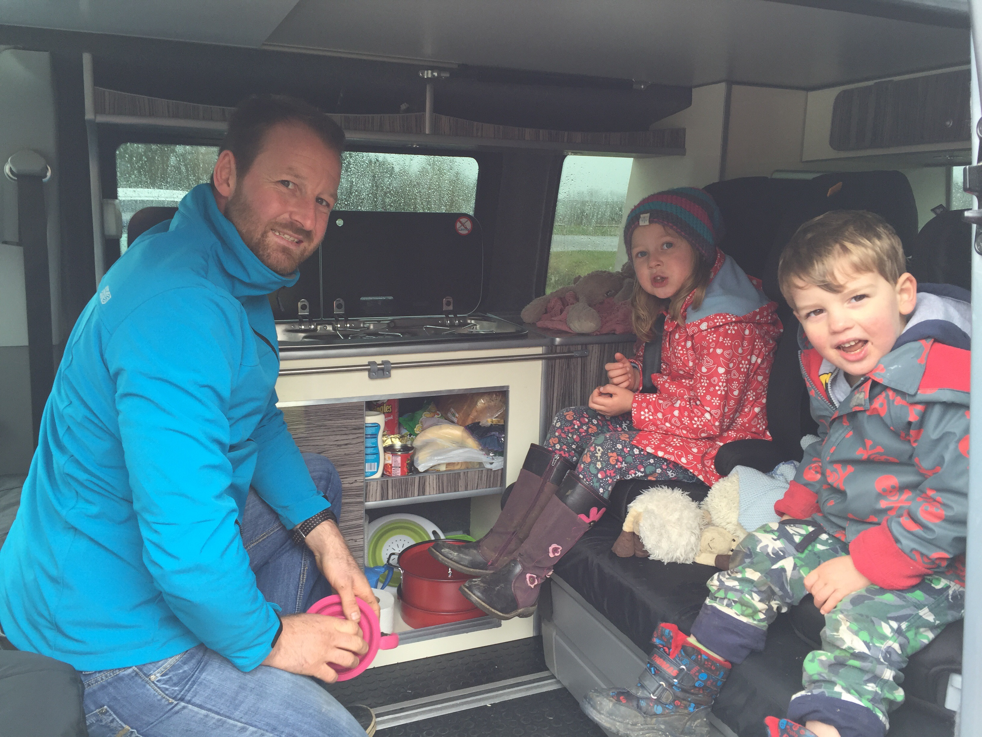 On one of our campervan travel trips, Dave and the kids sitting in the kitchen area of the van, all looking and smiling as he gets the kettle out ready to put on the hob and make a cup of tea.