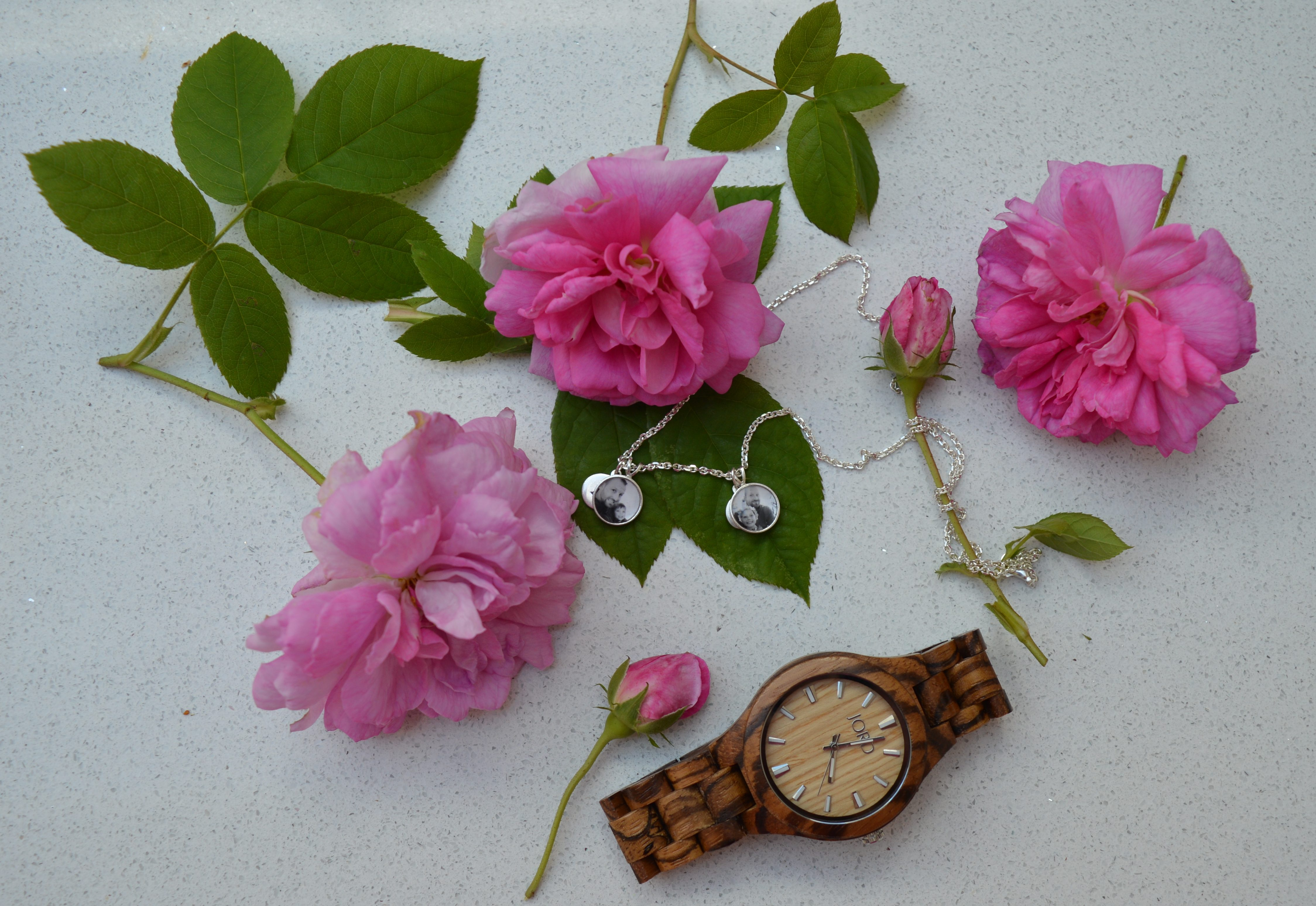 A beautiful shot from above of my photogem necklace with a watch lying among some big pink roses on a white background.