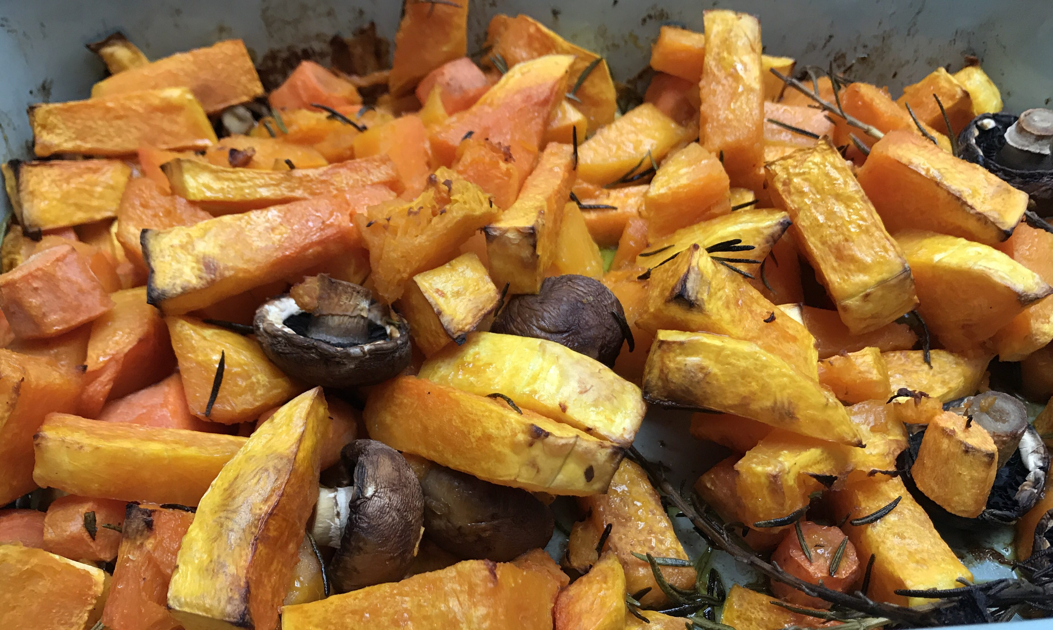 An oven roasted dish of bright yellow butternut squash, orange carrots and juicy chesnut mushrooms.