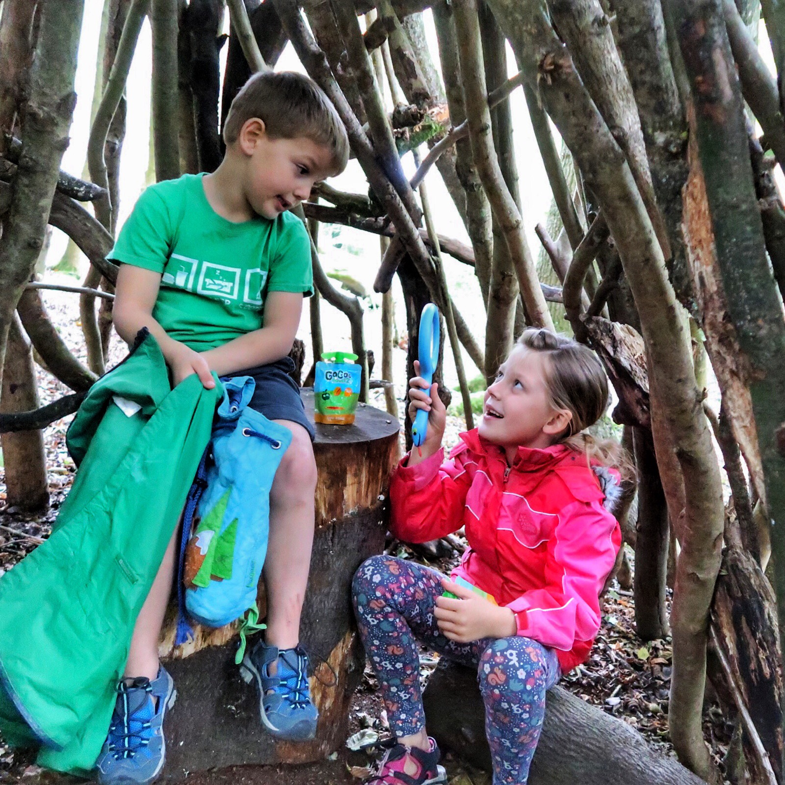 The children sitting in a stick den looking at each other through a magnifying glass with a packet of GoGo SqueeZ next to them.