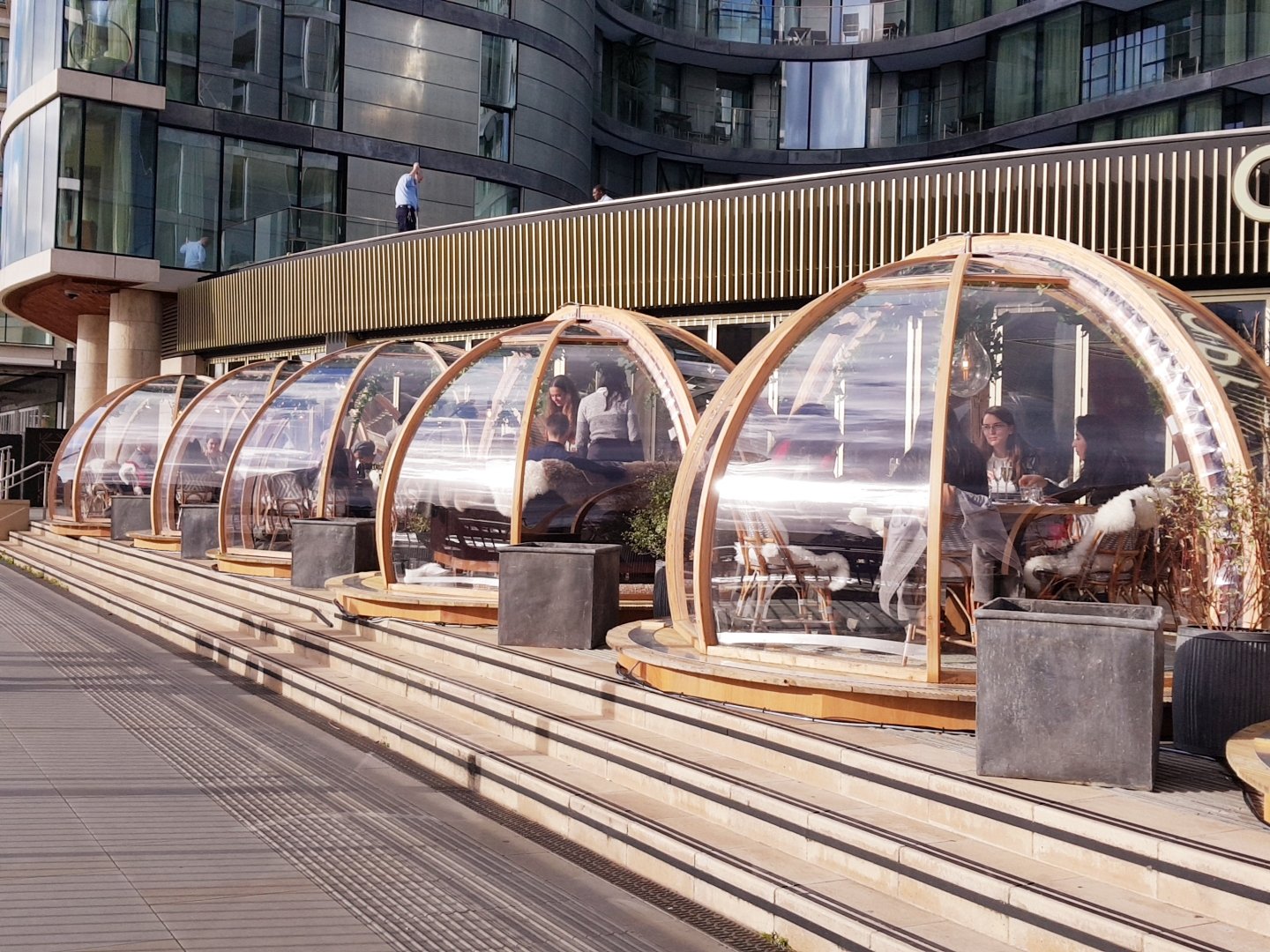 A photo of a very cook waterfront restaurant with very cool outdoor glass dining pods to stay warm and still enjoy the view!