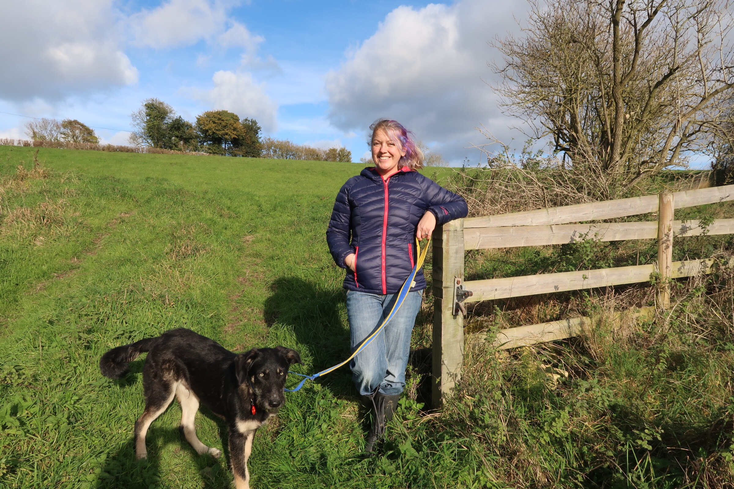 Me in a blue puffa jacket with pink trim from Millets leaning on a gate and holding our dog Barney on the lead.