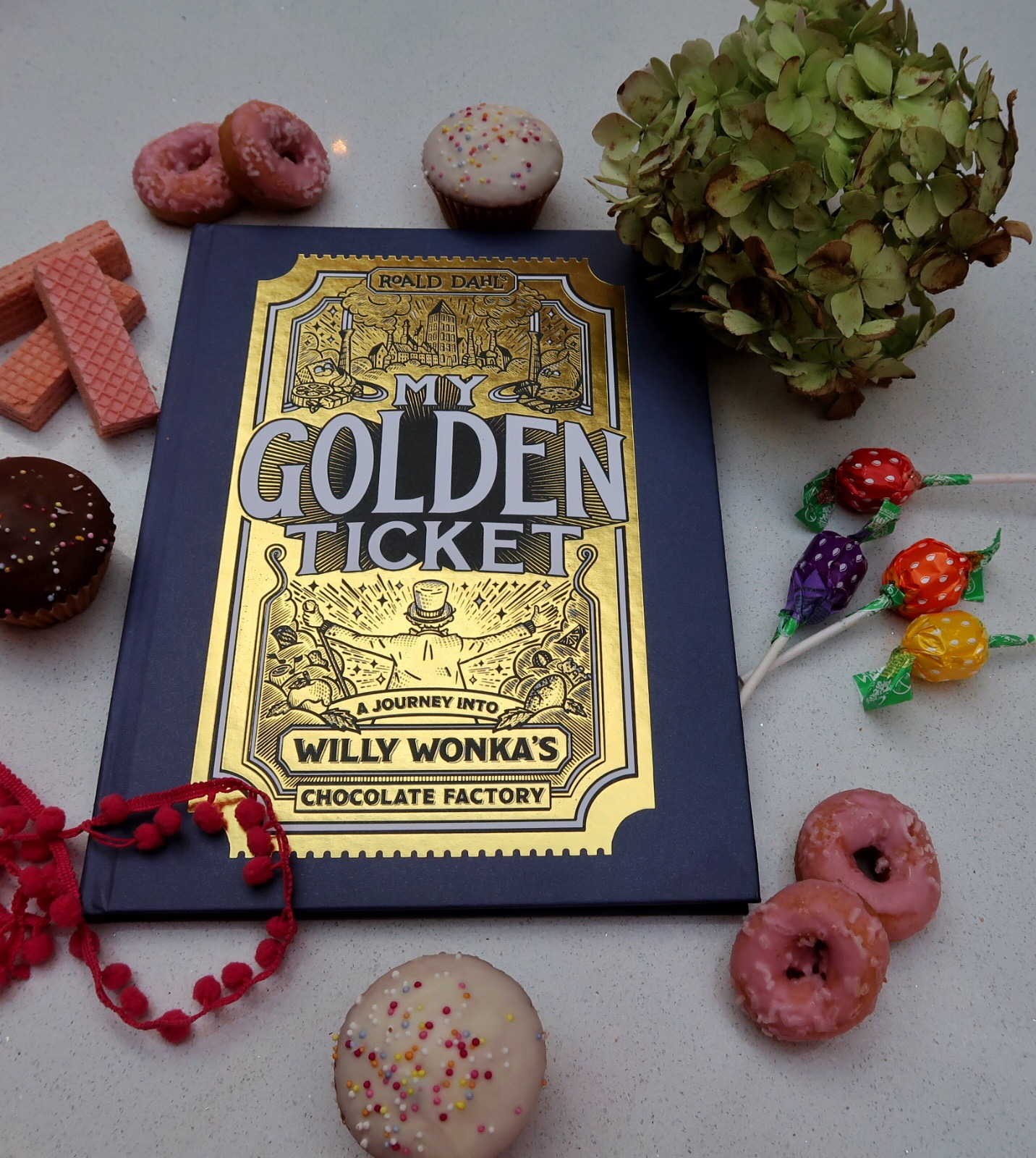 The beautiful blue and gold cover of the My Golden Ticket hardcover book surrounded by sweet treats!