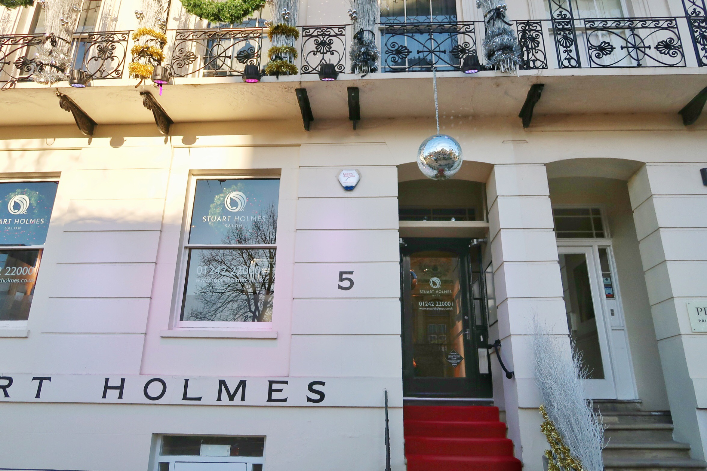 The lovely exterior of the Stuart Holmes salon with the Christmas decorations on the wrought iron balcony and the giant disco ball above the door.