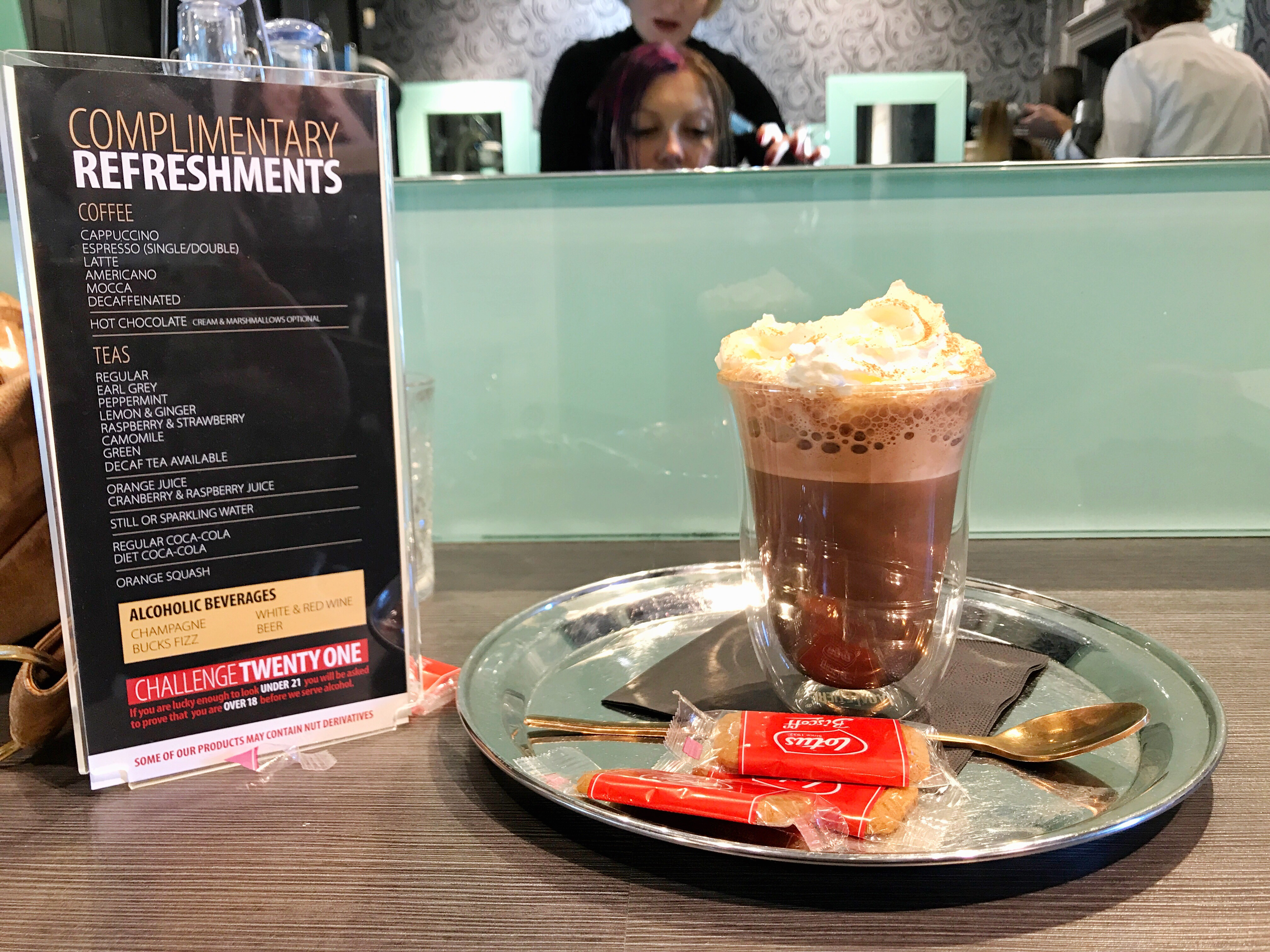 The hot chocolate with cream that I had next to a menu of the complimentary drinks that Stuart Holmes offers which includes a variety of coffees and soft drinks with alcoholic options available for £2.00 a glass.