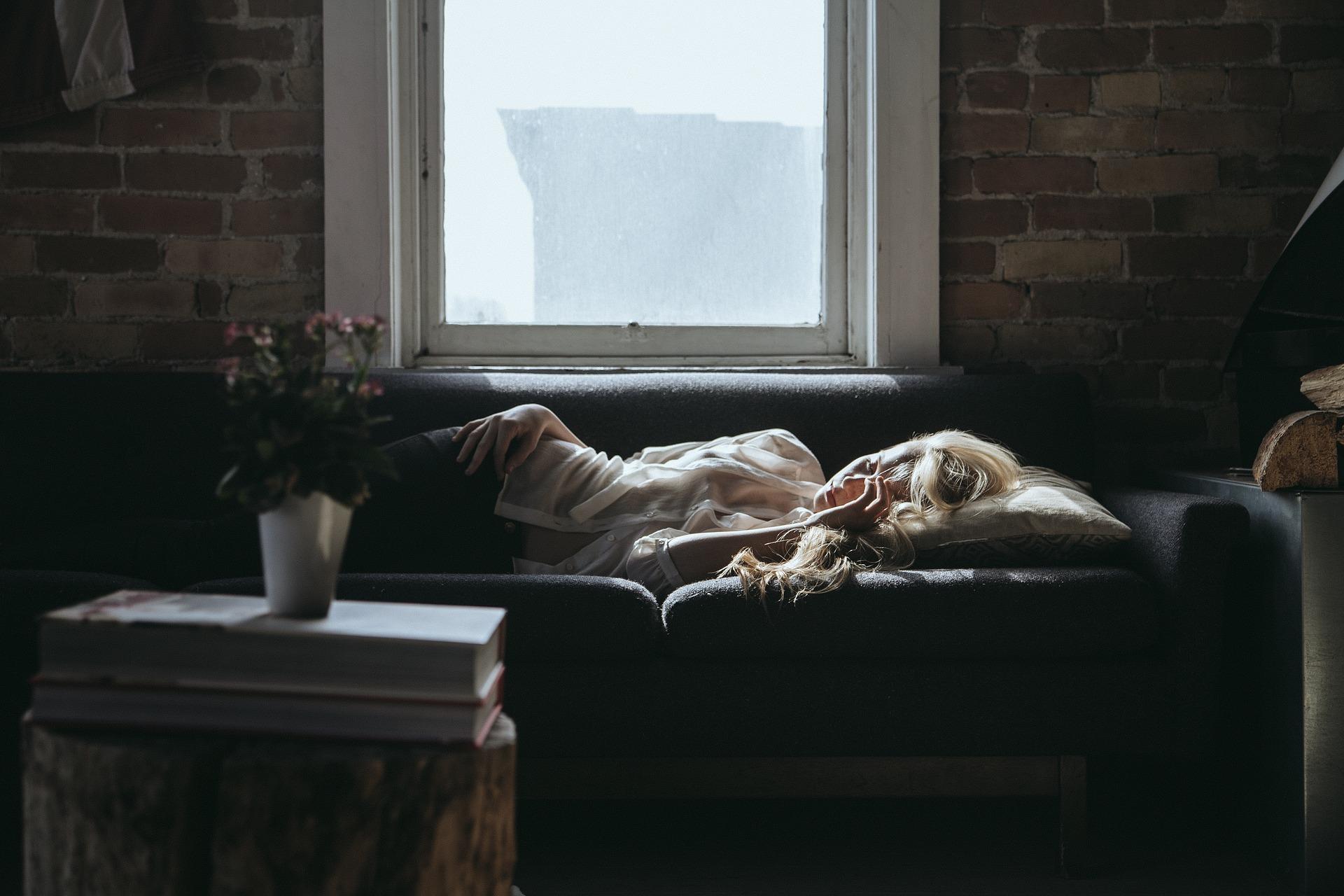 A woman fast asleep on the sofa.