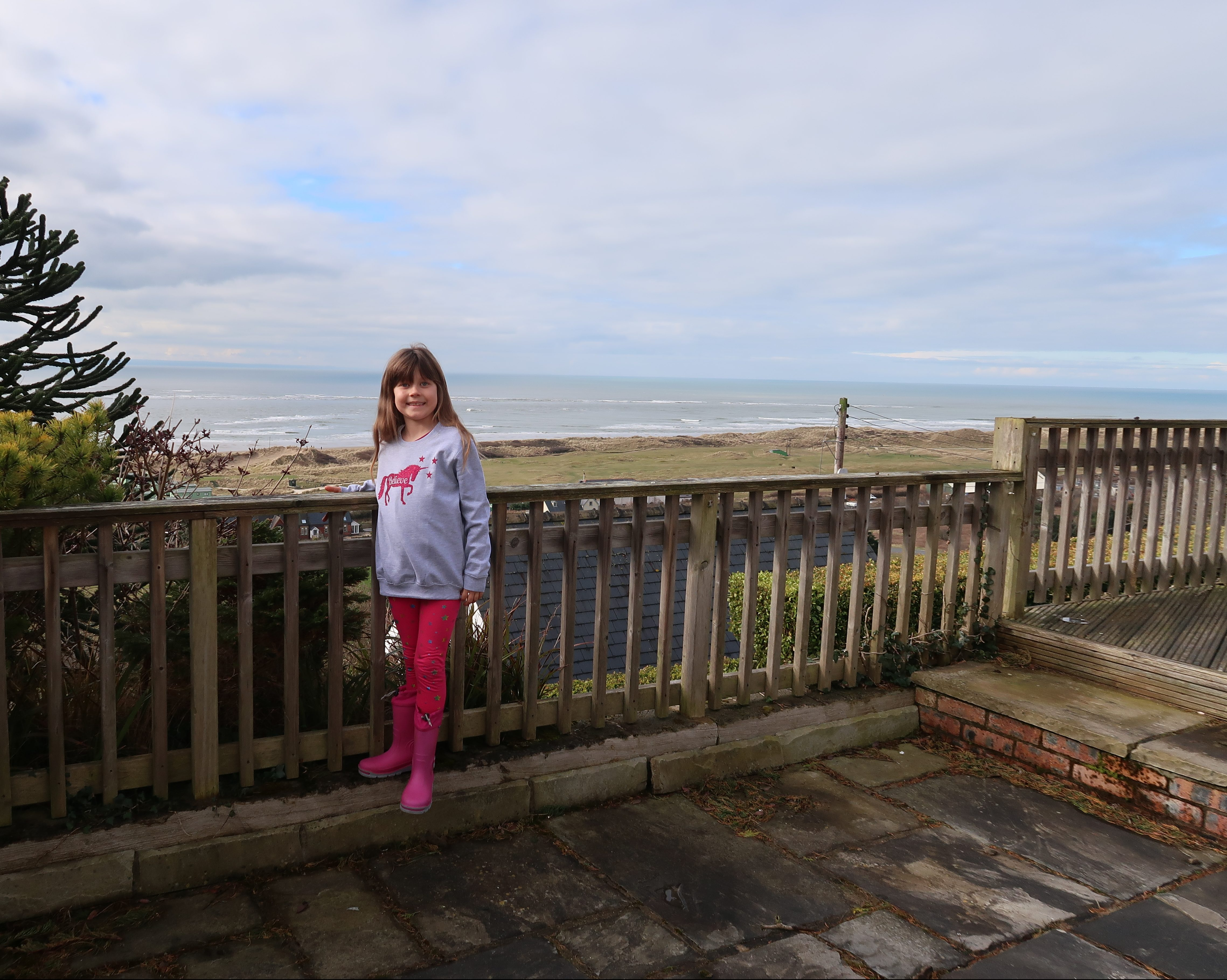 My daughter posing in a grey long sweater with a sparkly pink unicorn on, she's also wearing pink leggings and pink wellies, she's leaning against a wooden railing with a backdrop or sand dunes and sea stretching off to the horizon. The sky is full of white cloud with little patches of blue in between.
