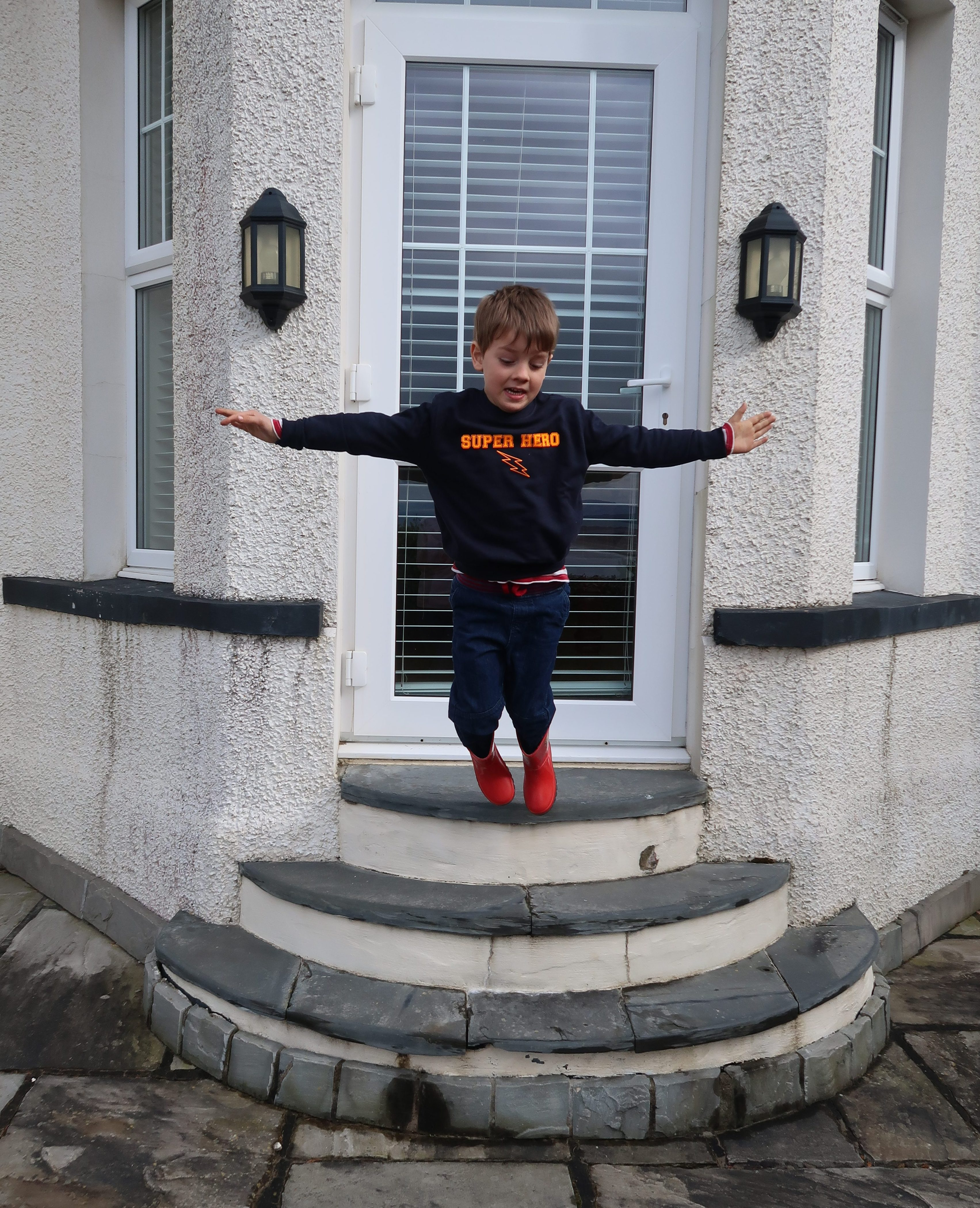 My son is in a dark blue jumper with the words super hero emblazoned across the front in neon orange, he is also wearing jeans and red wellies and the photo captures him in mid air as he jumps from the top of three slate steps leading to a door in a white house. His arms are stretched out to either side and he's looking down and away from the camera as he prepares to land.
