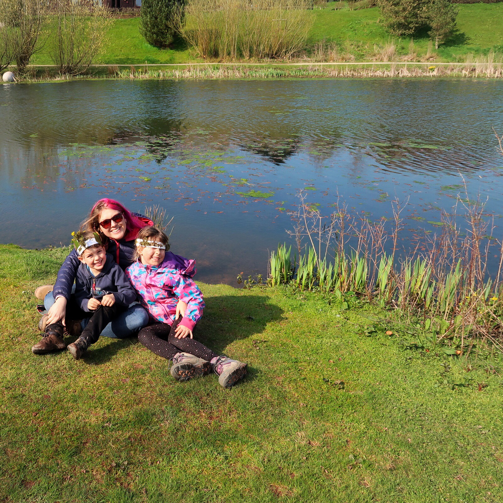 Myself and the children having a hug sitting on the grassy bank of another lake.