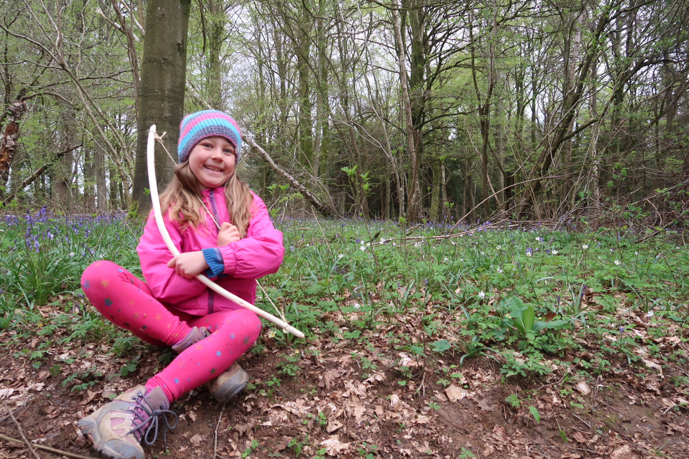 My daughter sitting down in a wood, behind her is a beautiful carpet of bluebells and white flowers. She is beaming as she holds a bow that she made herself from a stick and some twine. She is wearing pink leggings, a pink coat, walking boots and a woolly beanie hat.