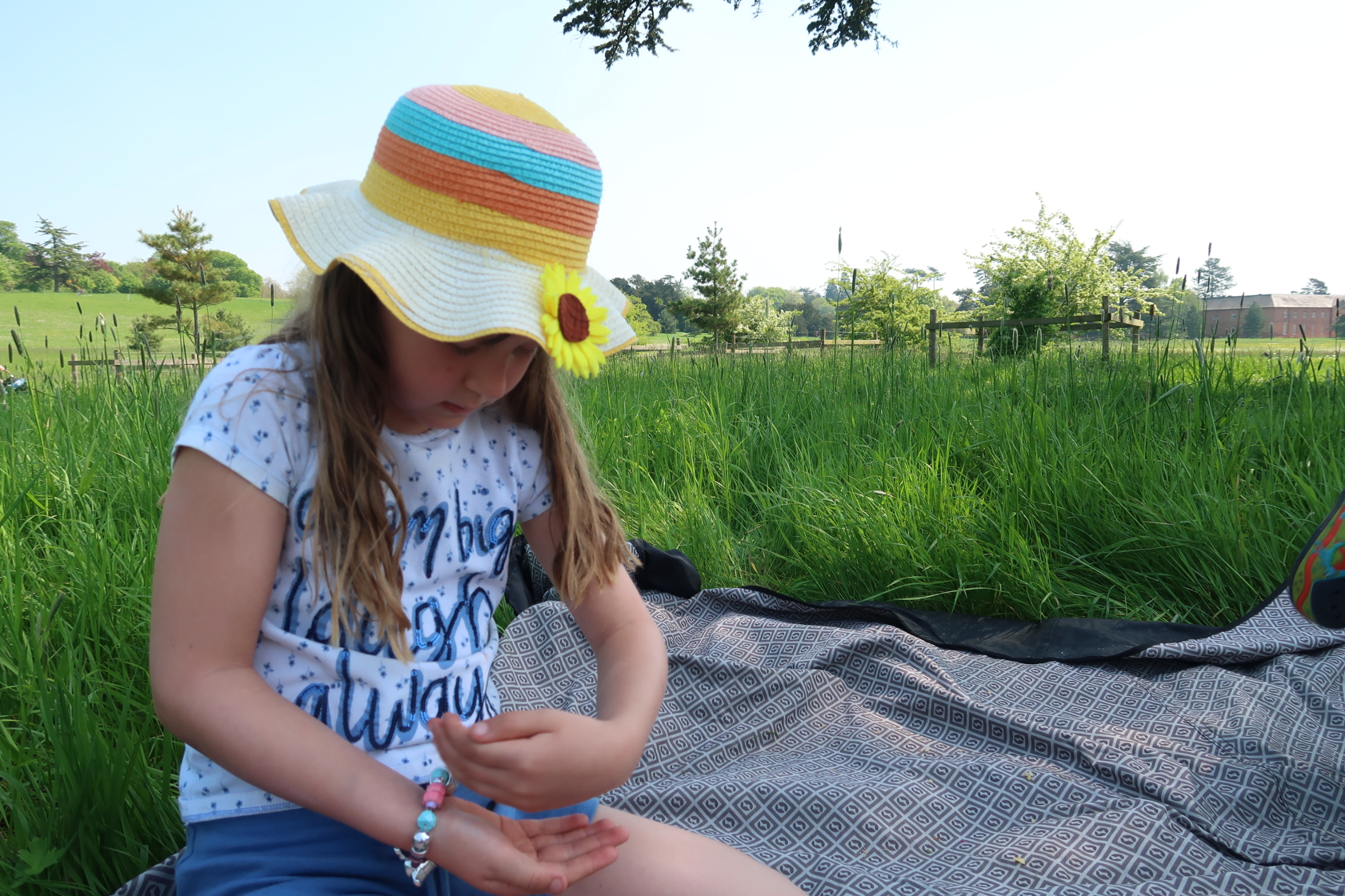 My daughter sat close to the camera on the left side of the frame wearing a bright coloured, striped straw sun hat with a sunflower on. She is on a blanket in a meadow of long, lush green grass, intently studying a tiny beetle that landed on her hand. It's sunny and the sky is blue.