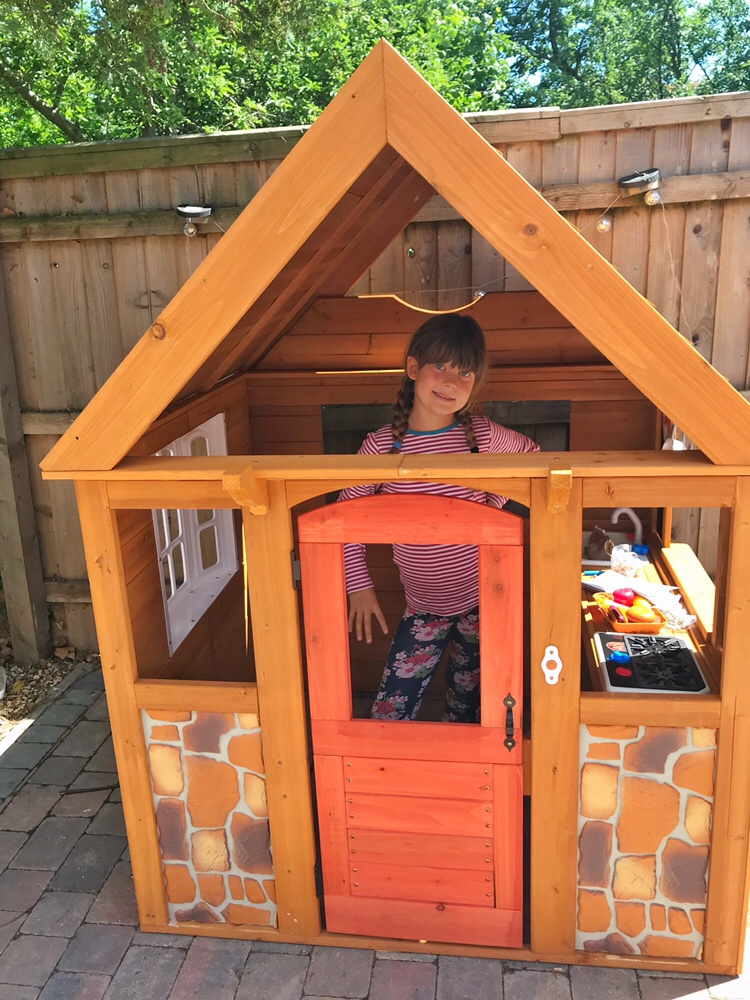 Nearly there! My daughter standing in the Stoney Creek Playhouse from KidKraft as it is partly assembled.