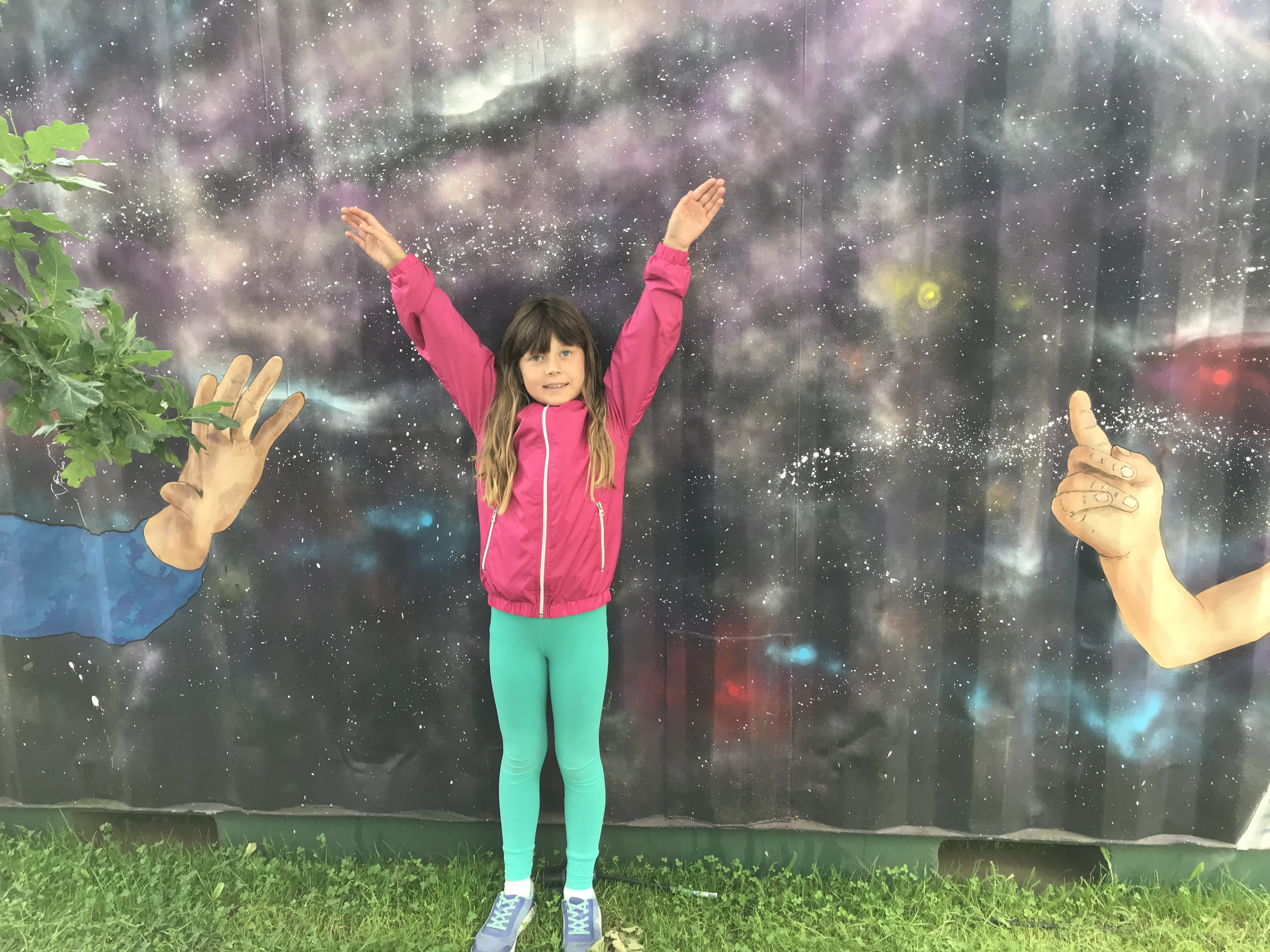 This is my daughter standing in front of a big metal shipping container which has been graffitied with a solar system. We were visiting a science festival.