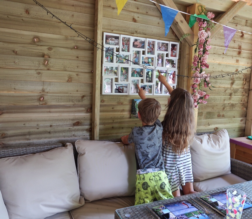 A photo on my son and daughter looking at the Snapfish photos, on their knees on the rattan sofa and pointing to their favourites. My son wears neon green and grey Star Wars pyjamas and my daughter a blue and white stripy dress.