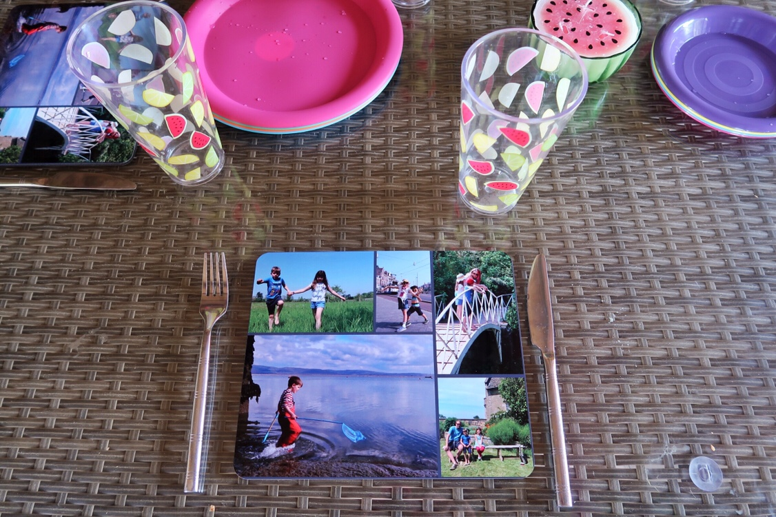 A close up of the photo placemats I made using Snapfish laid up with cutlery, bright coloured plates and plastic tumblers scattered with illustrations of watermelon and lemon slices.