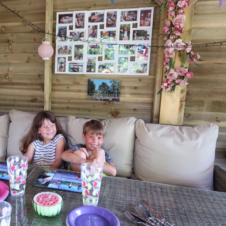 Two cheeky little children sitting under the photo display I made out of the Snapfish products I used waiting for their bbq dinner to be ready. Smiling away with big cheesy grins.