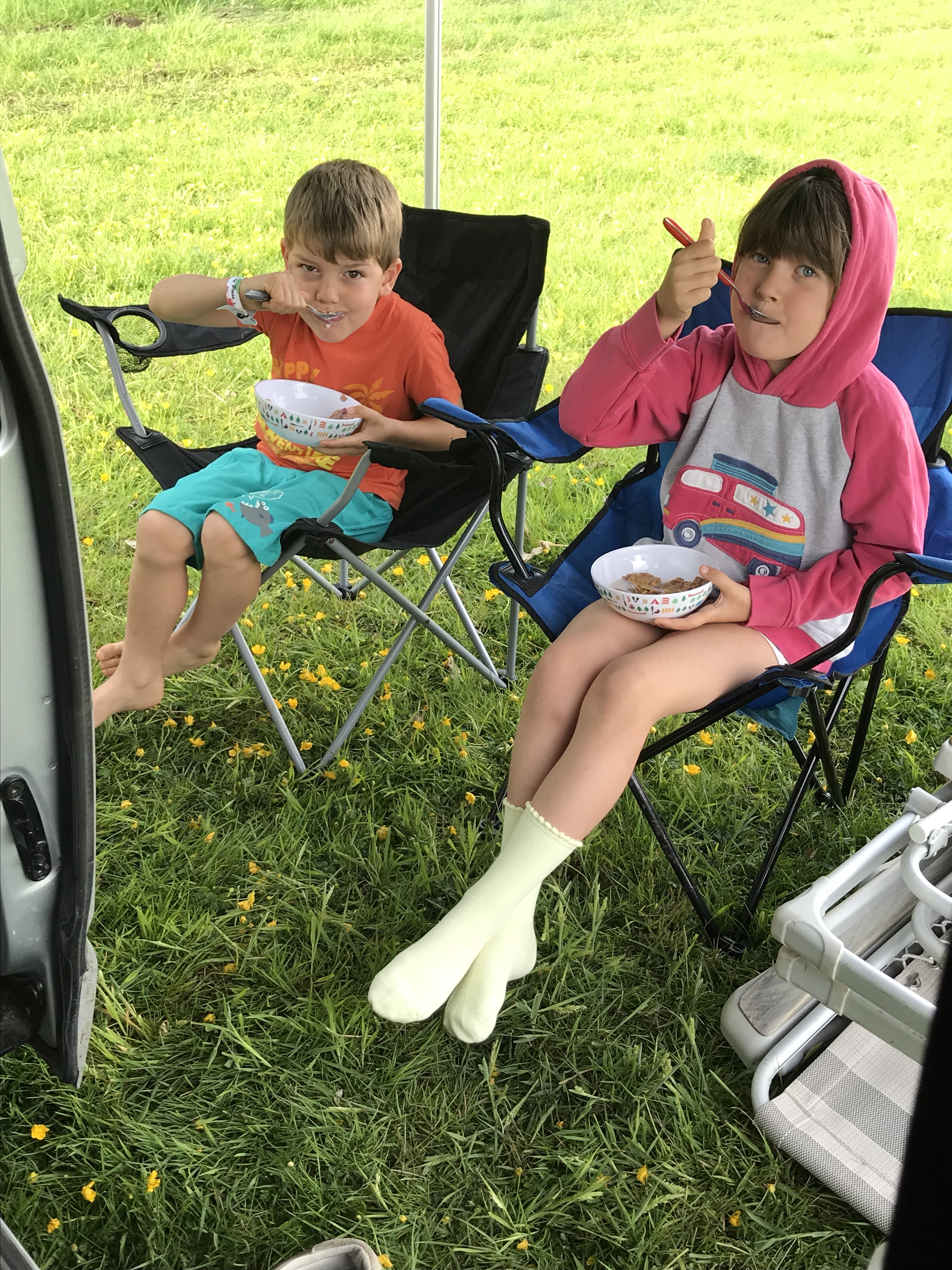 Both of my children sitting in camping chairs outside Wilma our campervan, eating bowls of cereal. They both have spoons in their mouths mid bite, and are looking at the camera. Keep siblings well fed to avoid fighting!