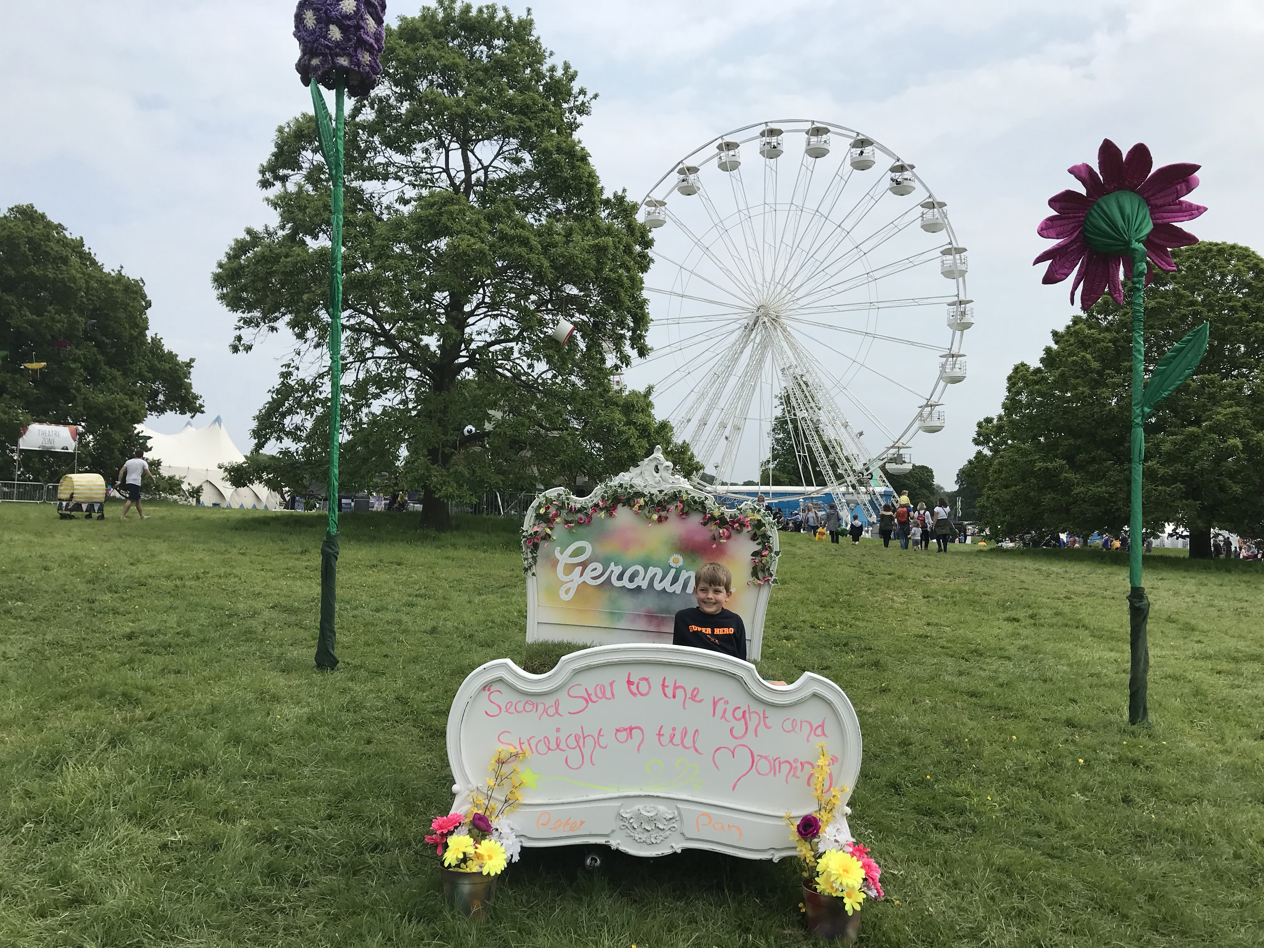 My son, sitting on a bed on the grass at Geronimo Festival, with 'Second star to the right and straight on til morning' written on the foot of the bed. Giant flowers around him and a Ferris wheel behind.