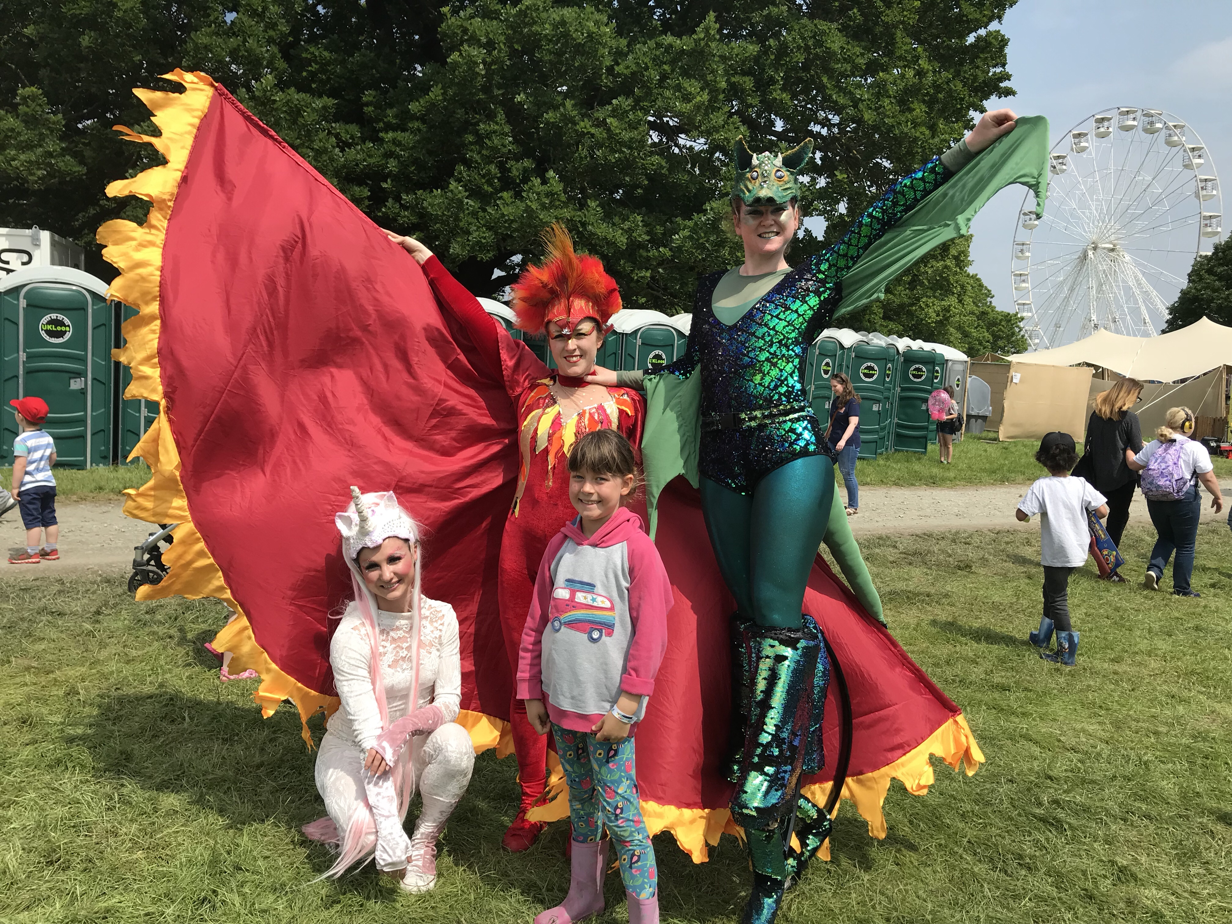Some of the extravagantly costumed characters at Geronimo Festival, a unicorn, a red fiery creature with huge woods and a green dragon on stilts standing with my daughter.
