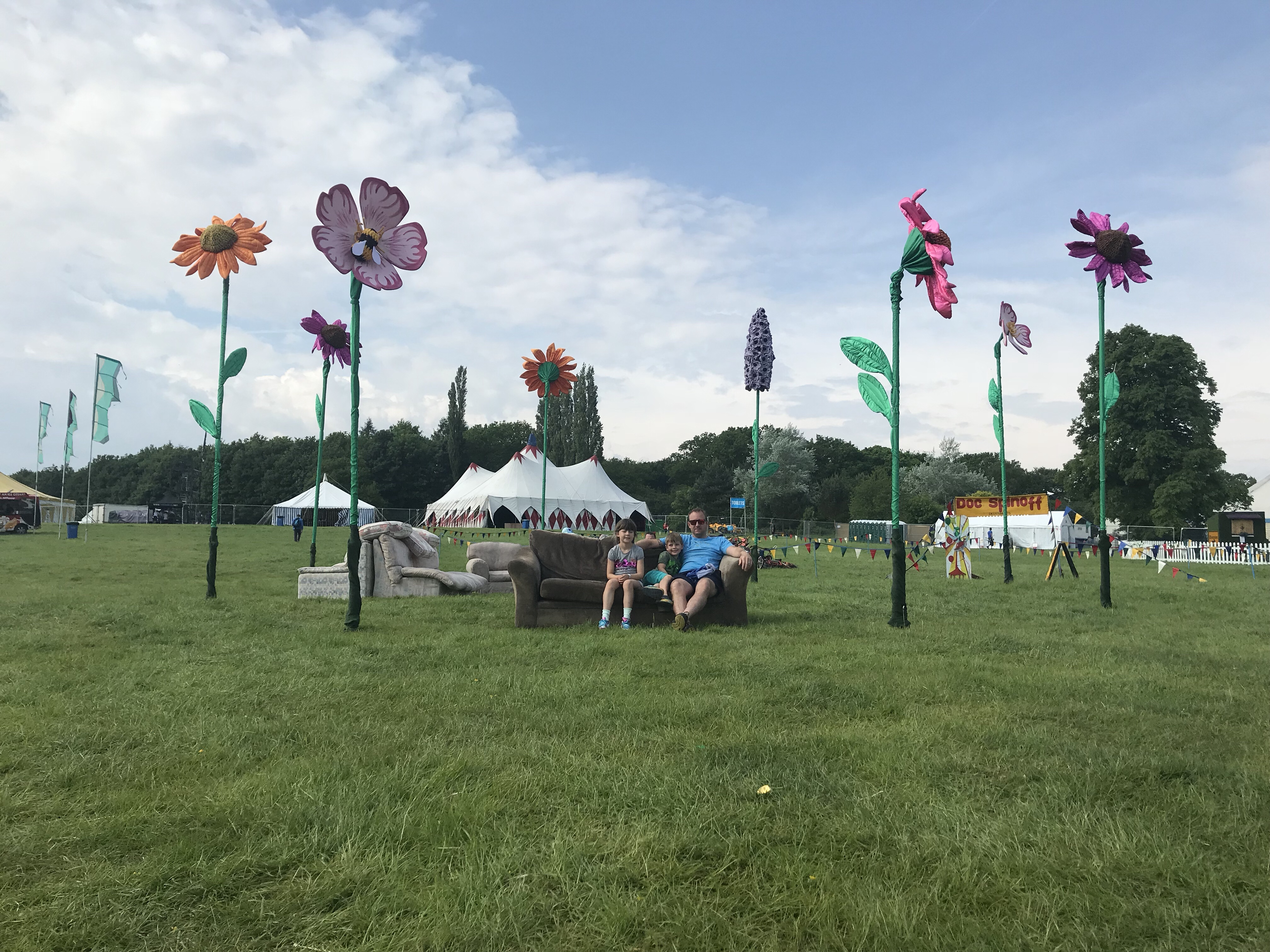 My husband and two children sitting on a sofa outdoors at Geronimo Festival with giant flowers all around them.