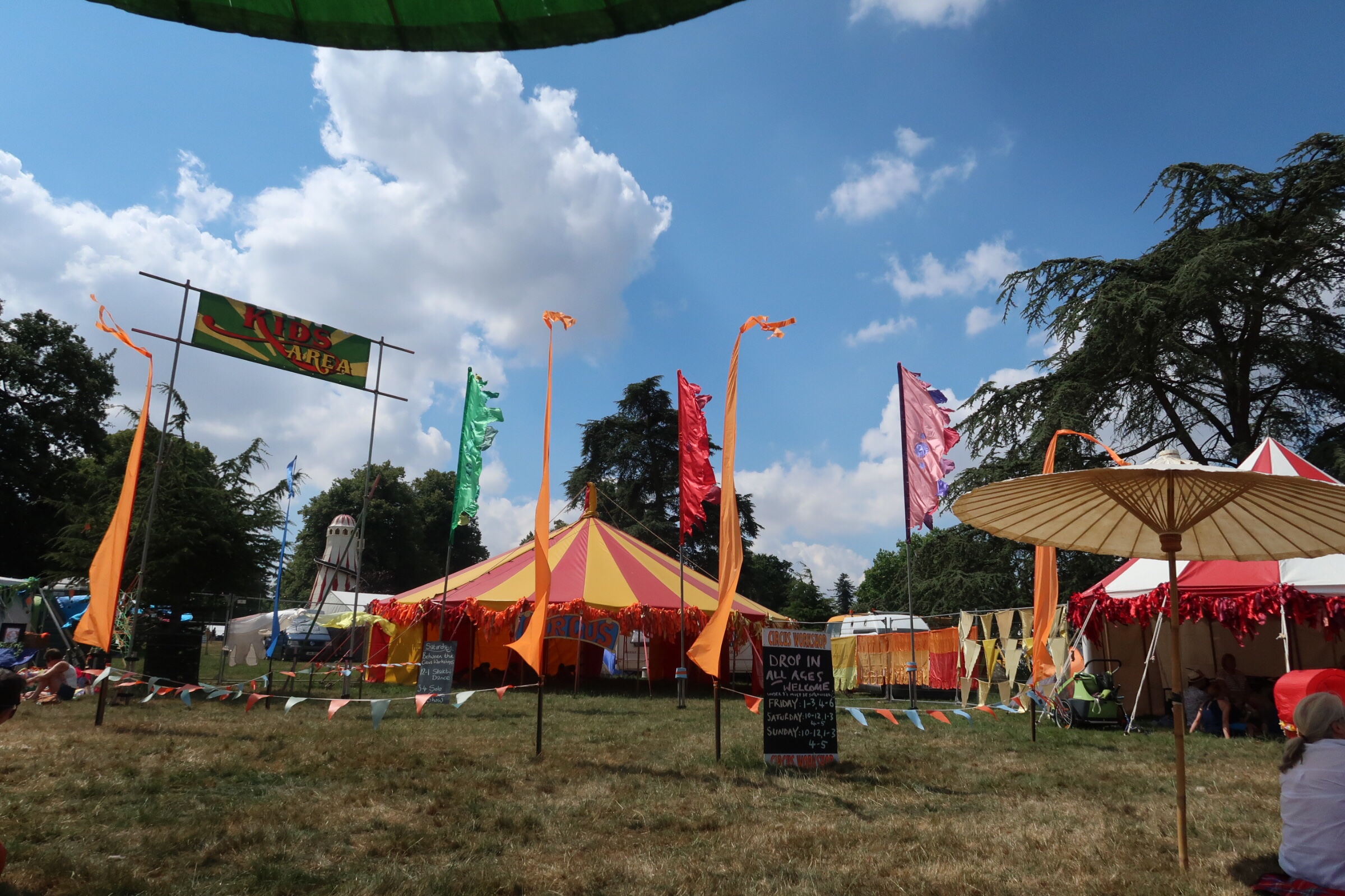 The kids area at Cornbury festival with the brightly coloured circus tents all around and bright blue sky above.