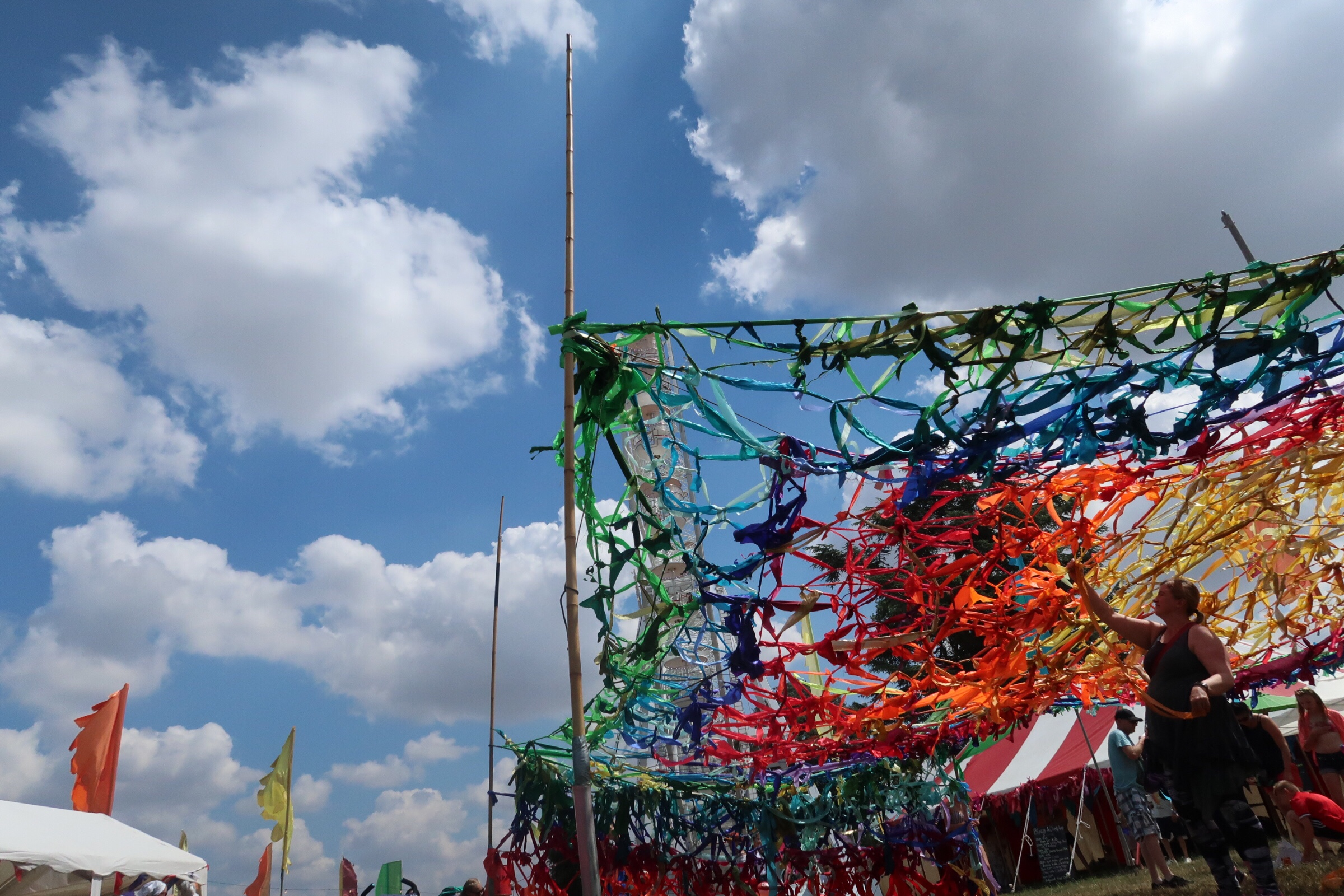 A lady adding to the brightly coloured rainbow netting canopy at Cornbury Festival.