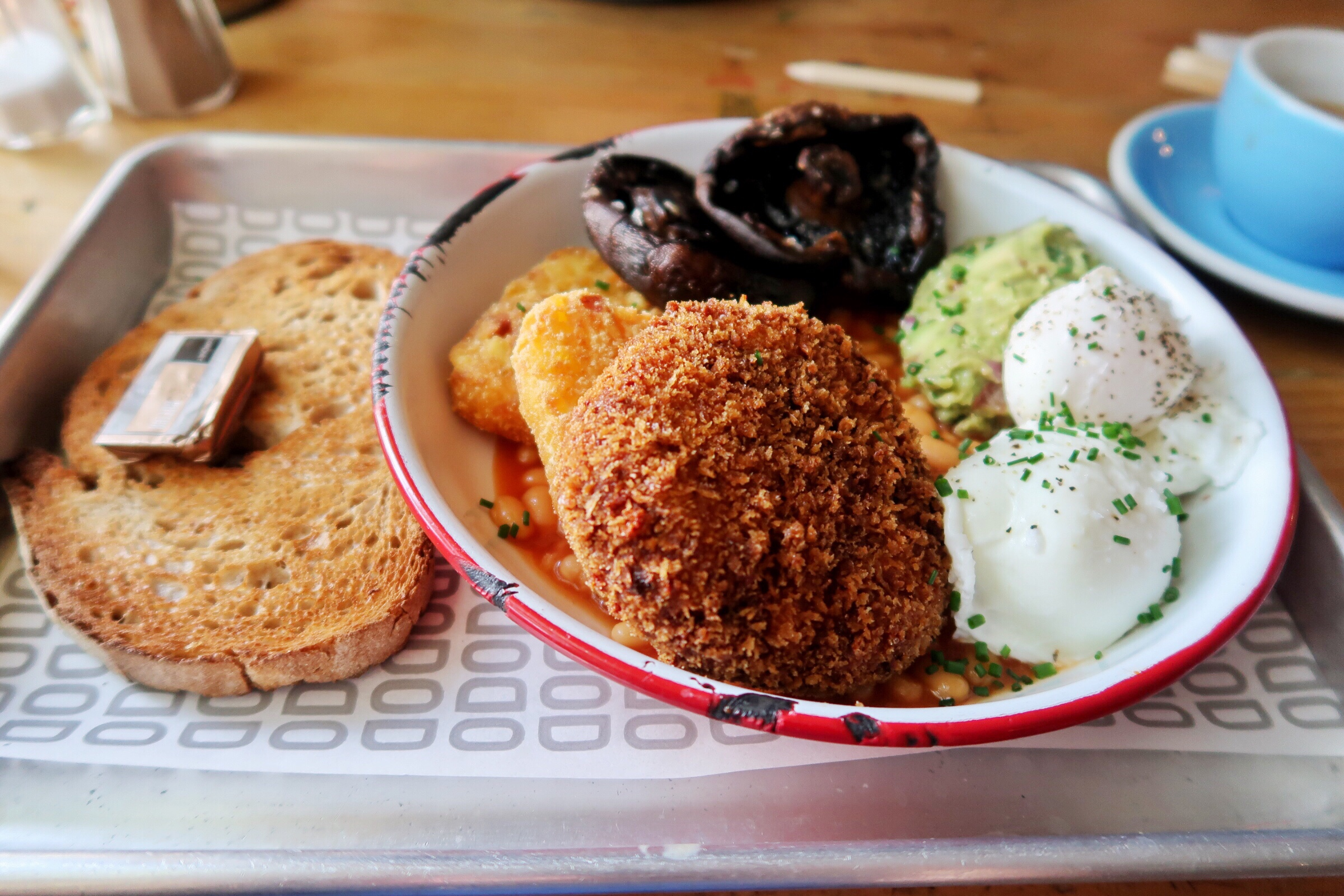 The absolutely delicious looking Mighty Vegetarian Brunch at the Bottle of Sauce in Cheltenham, consisting of perfectly poached eggs, a leek and cheddar crumbed patty, sourdough toast, amazing mushrooms, hashbrowns and beans. So yummy!