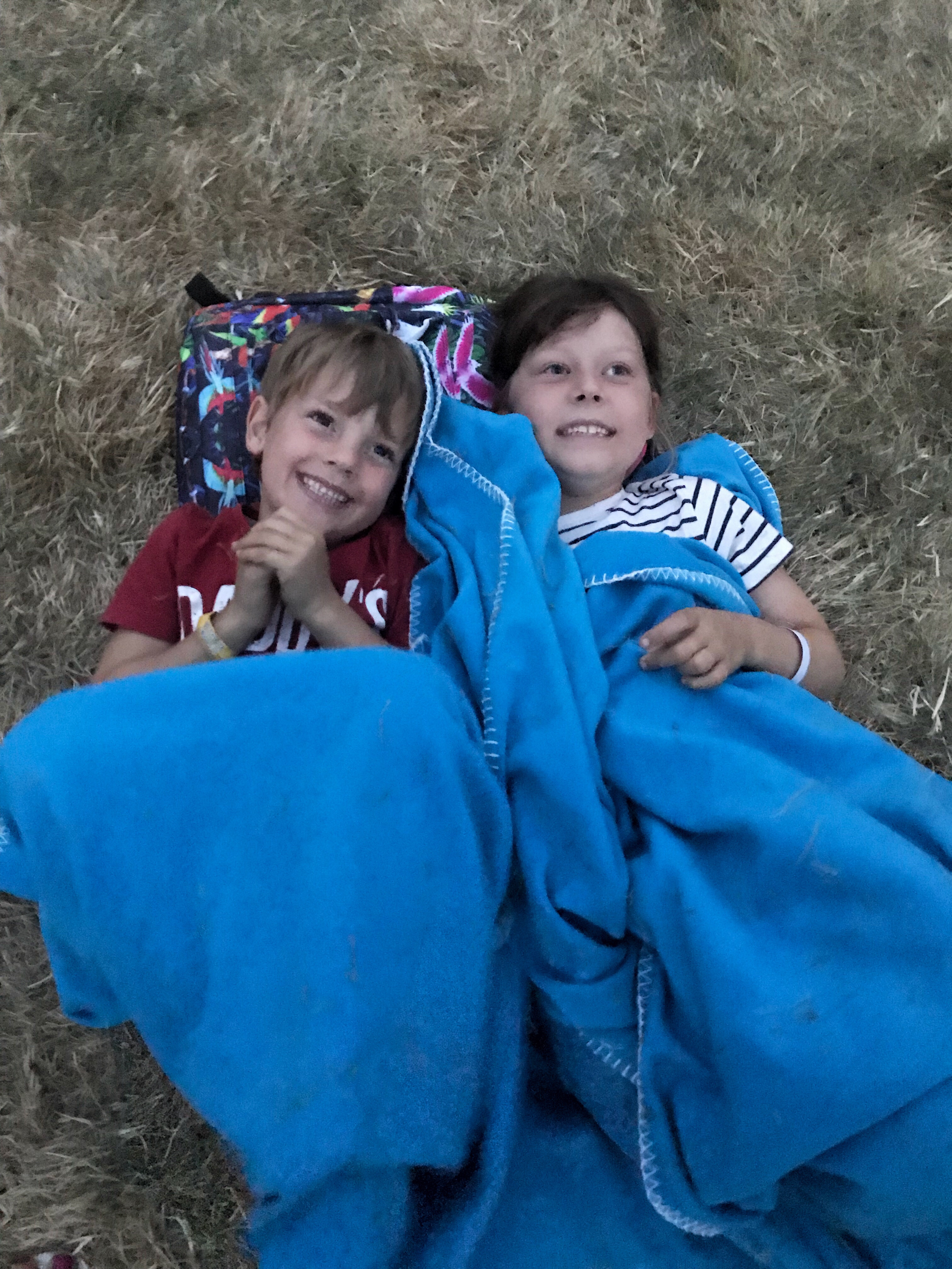 My two children snuggled in a blanket at dusk waiting for Alanis Morissette.