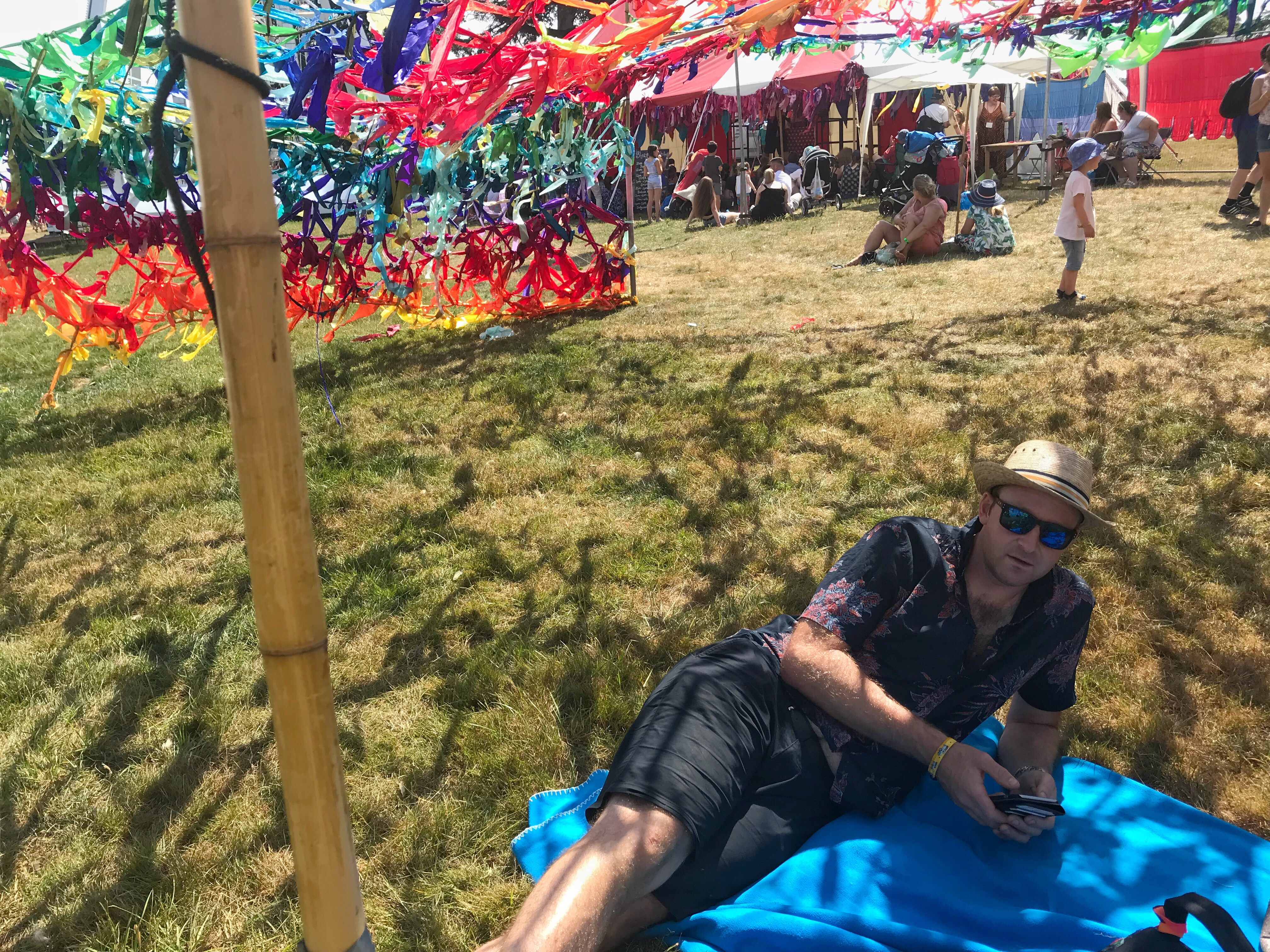 Relaxing at Cornbury Festival on a blanket under some rainbow coloured netting.