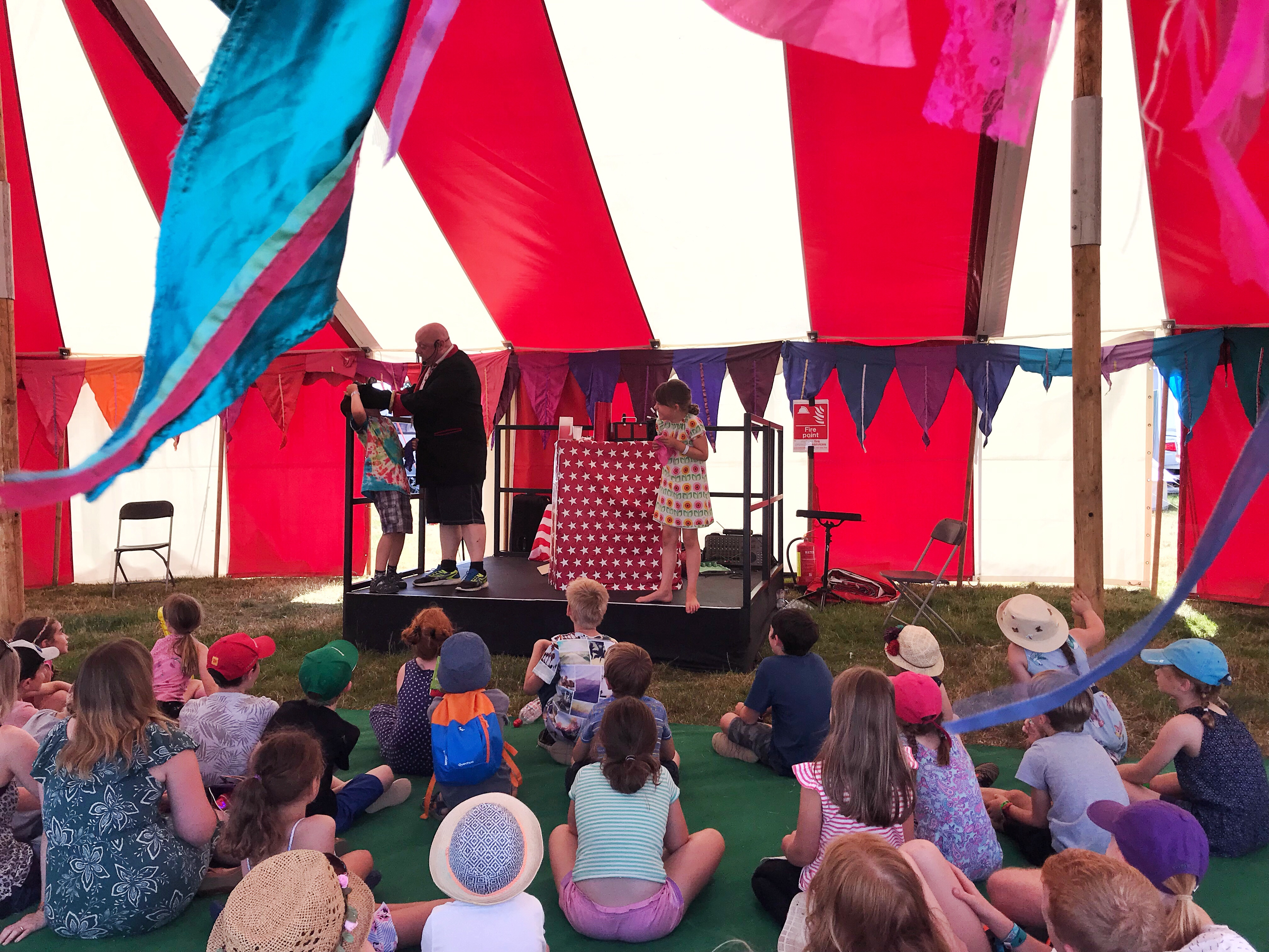 A group of children in a stripy red and white tent watching an entertainer at Cornbury Festival.