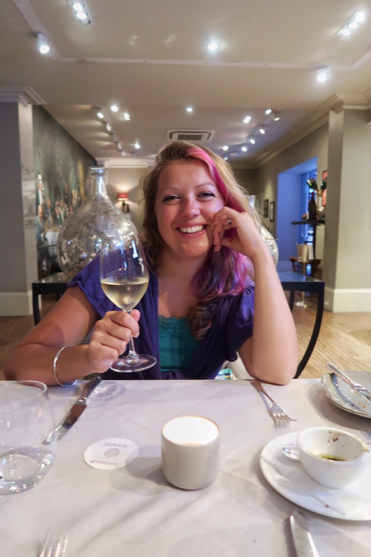 This is a photo of me holding a glass of wine in a restaurant and smiling into the camera, the blog post is about my experience of having a hysterectomy at a young age.