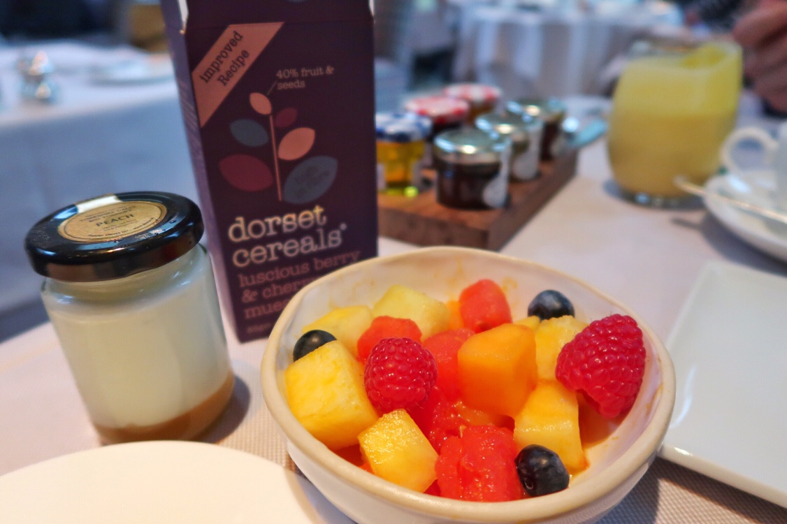 The delicious breakfast at the Vineyard hotel Newbury with fresh fruit in a bowl, a little jar of layered fruit and yoghurt and lovely Dorset cereal. Buyagift review.