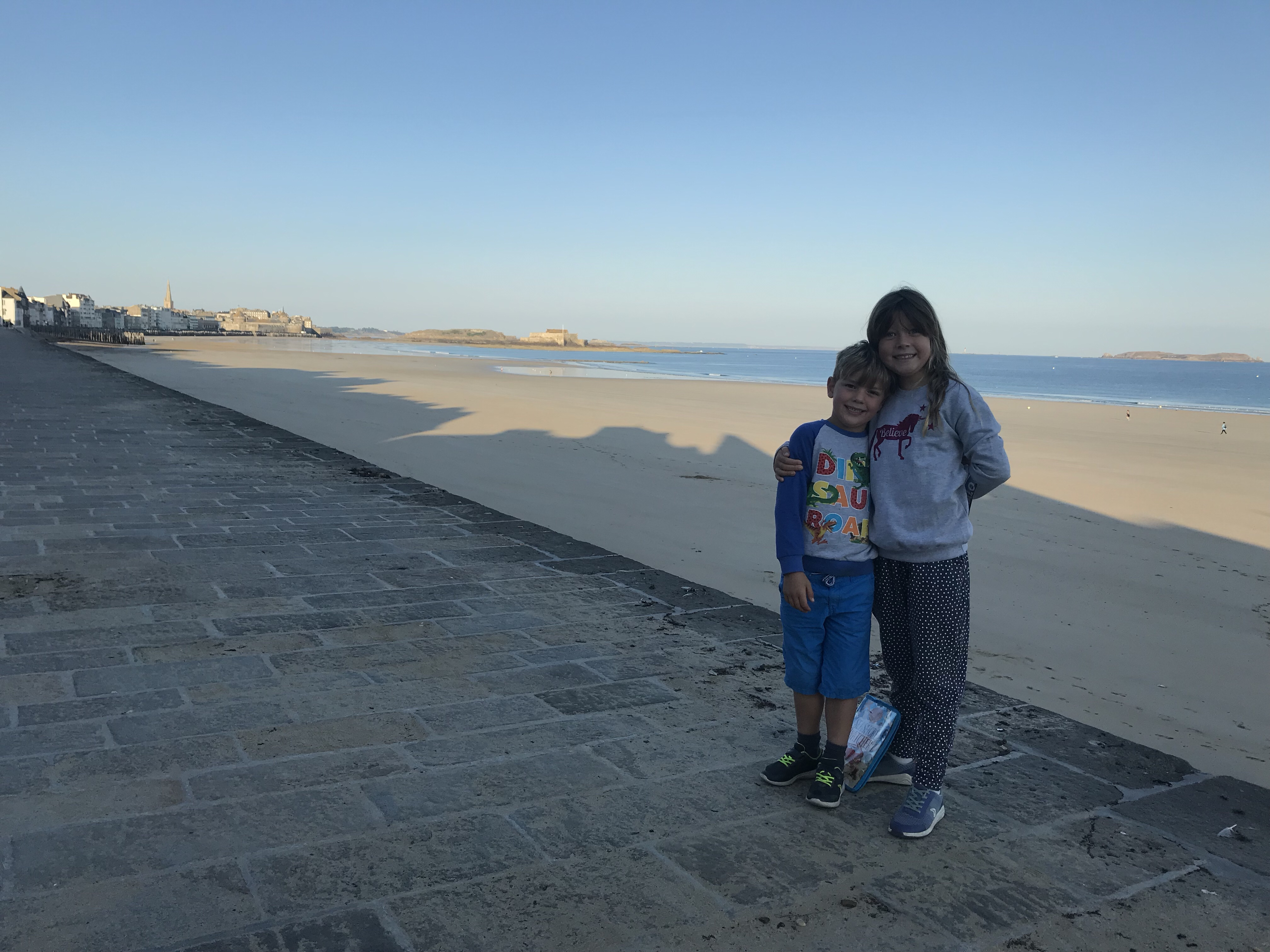 My two children standing with their arms around each other in front of a gorgeous stretch of beach and sea in France.
