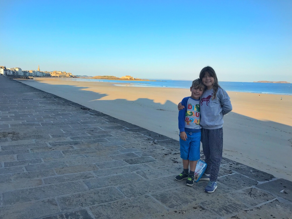 My two children standing in front of a gorgeous backdrop of seaside on holiday in France, a post talking about home education.