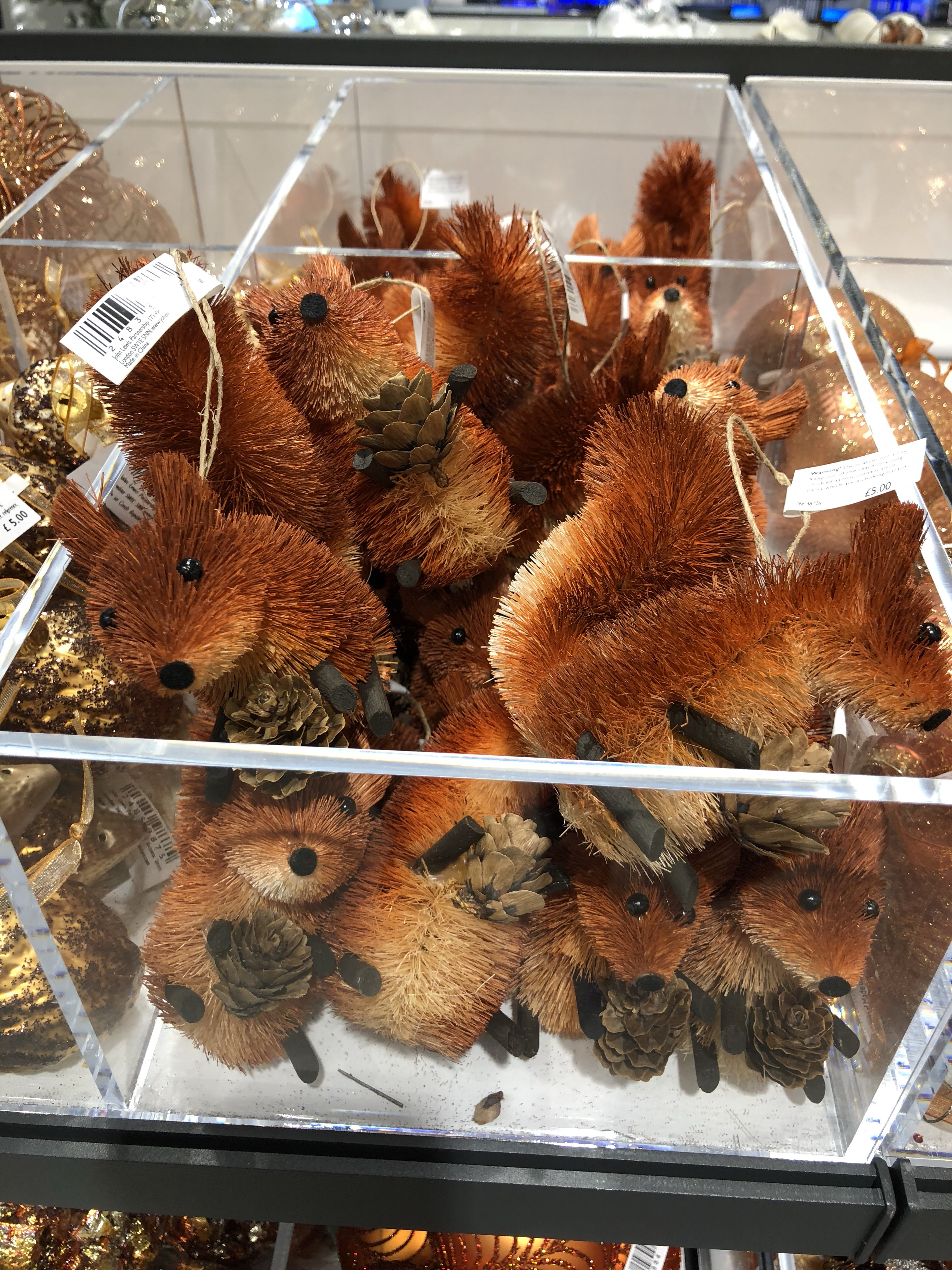 Little red squirrels holding pinecones in the Christmas decorations section at John Lewis Cheltenham