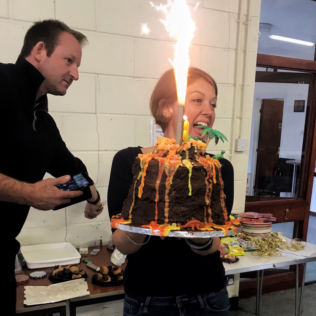 Me holding the giant volcano cake with a huge indoor firework sending sparks flying into the air. One of my science birthday party ideas.