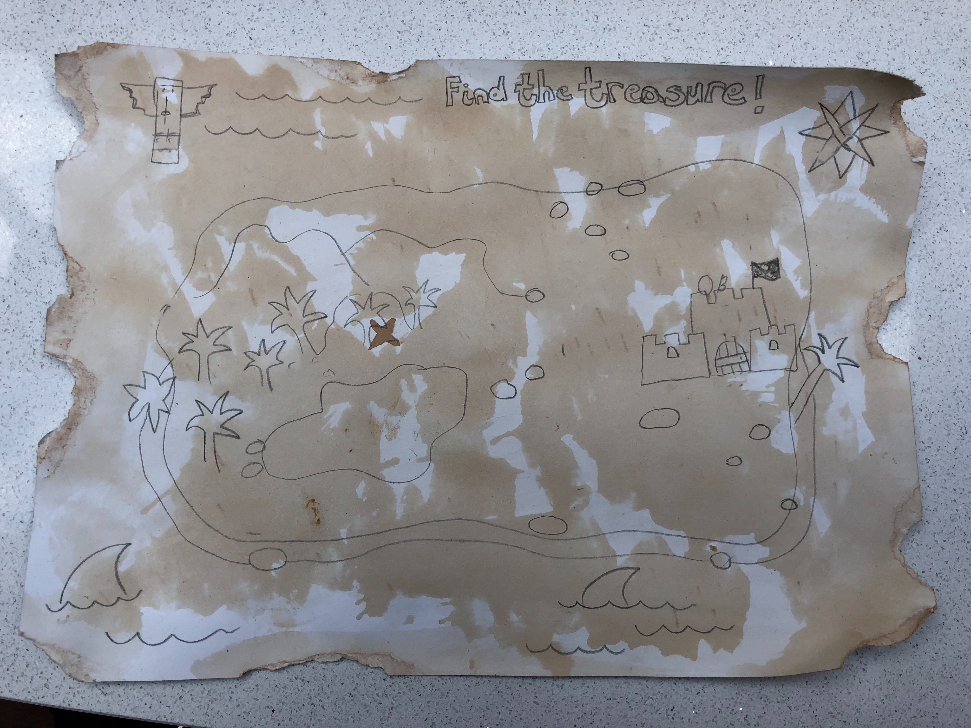 A tea stained 'treasure map' with a dark brown X marks the spot on. One of my science birthday party ideas,