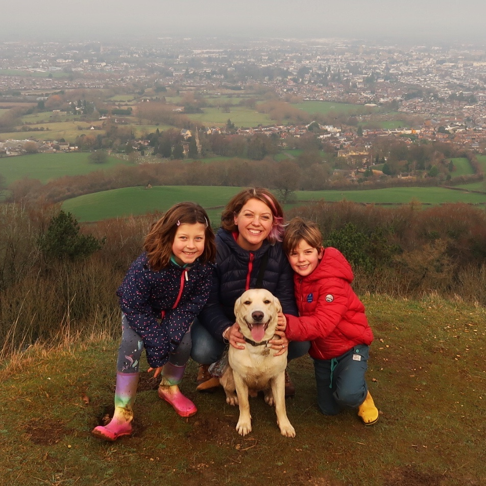 A photo of myself, the children and our yellow lab Hendrix on a hill with the whole town of Cheltenham behind.