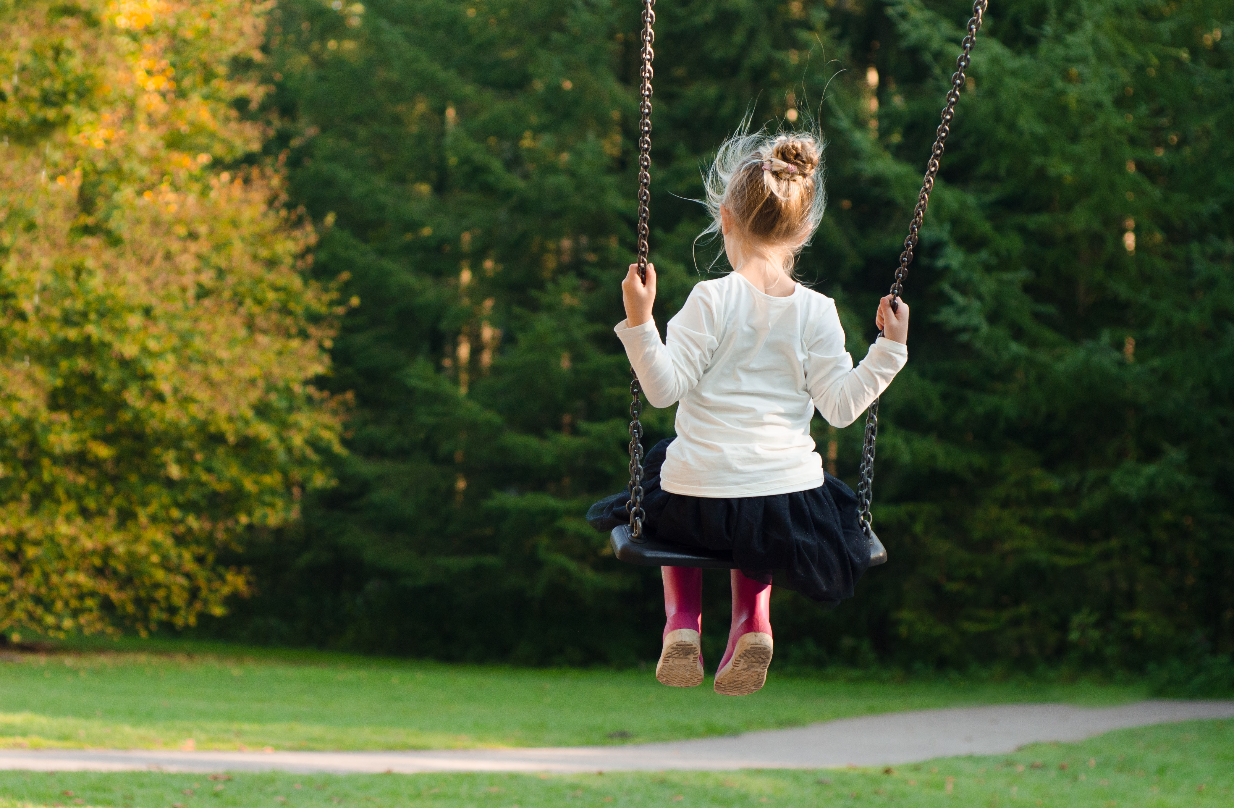 Tips to calm an anxious child. A stock photo of the back on a little girl with blonde hair in a bun and pink wellies sitting on a swing.