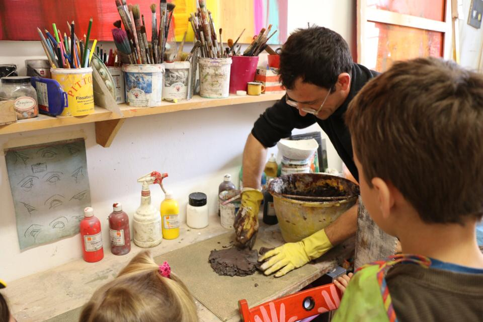 Getting hands on in the kids' club in Italy, a sculptor prepares some clay in a fun looking artist studio while the children watch on.