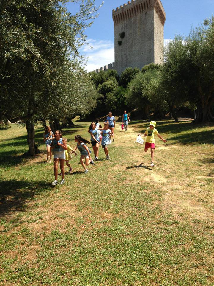 Happy children running excitedly down a grassy, tree-lined slope with a castle behind them.