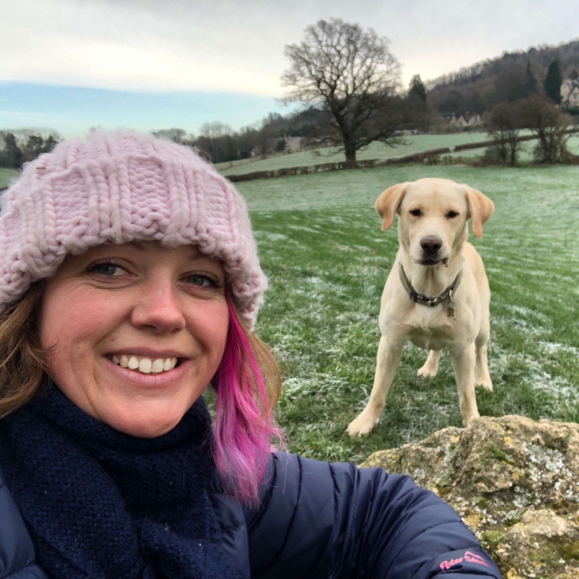 An unedited photo of me in the frost with a pink hat on looking at the camera and smiling with Hendrix our labrador behind me also looking at the camera.
