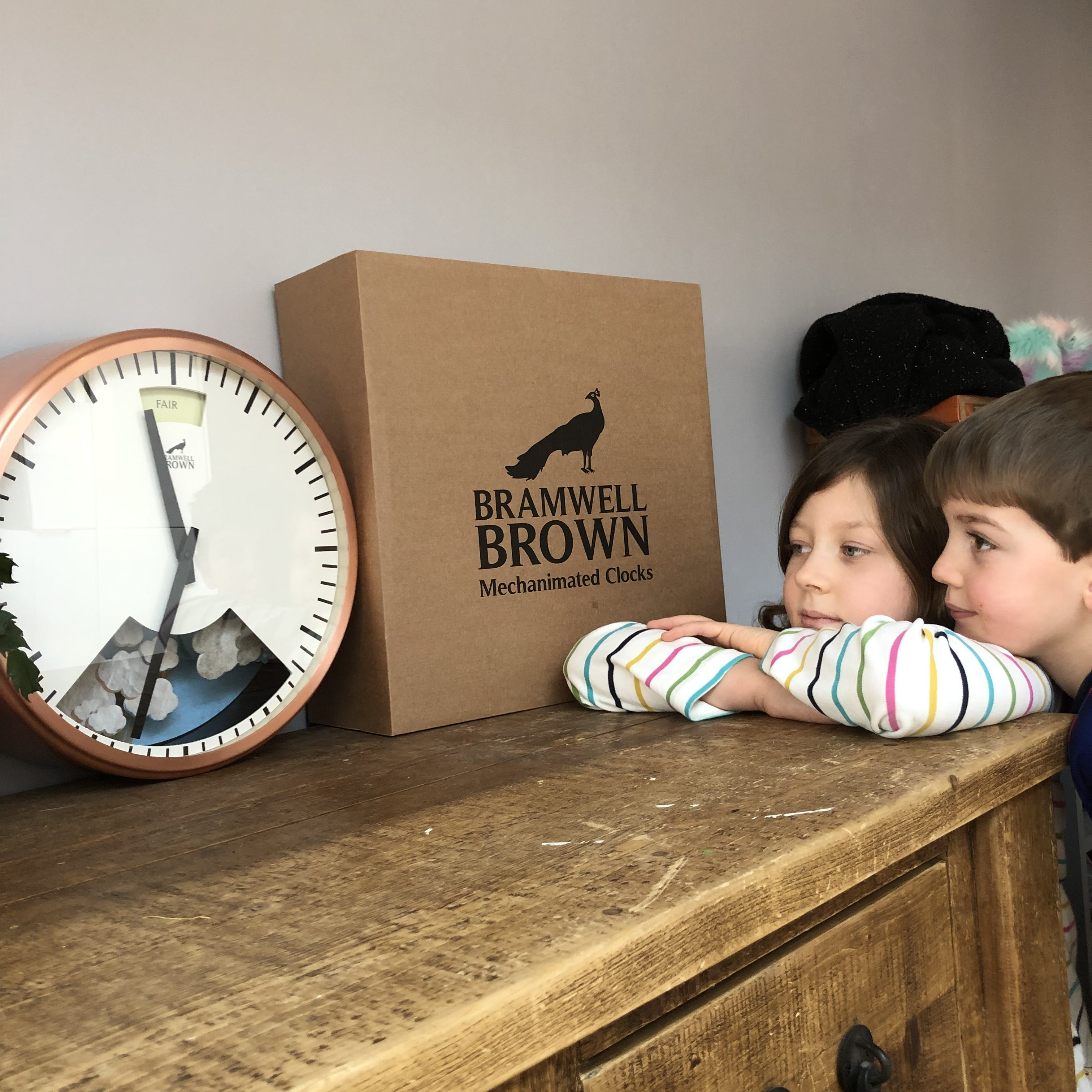 An unedited photo of my children leaning on a wooden dresser, looking at a clock that is also a barometer.
