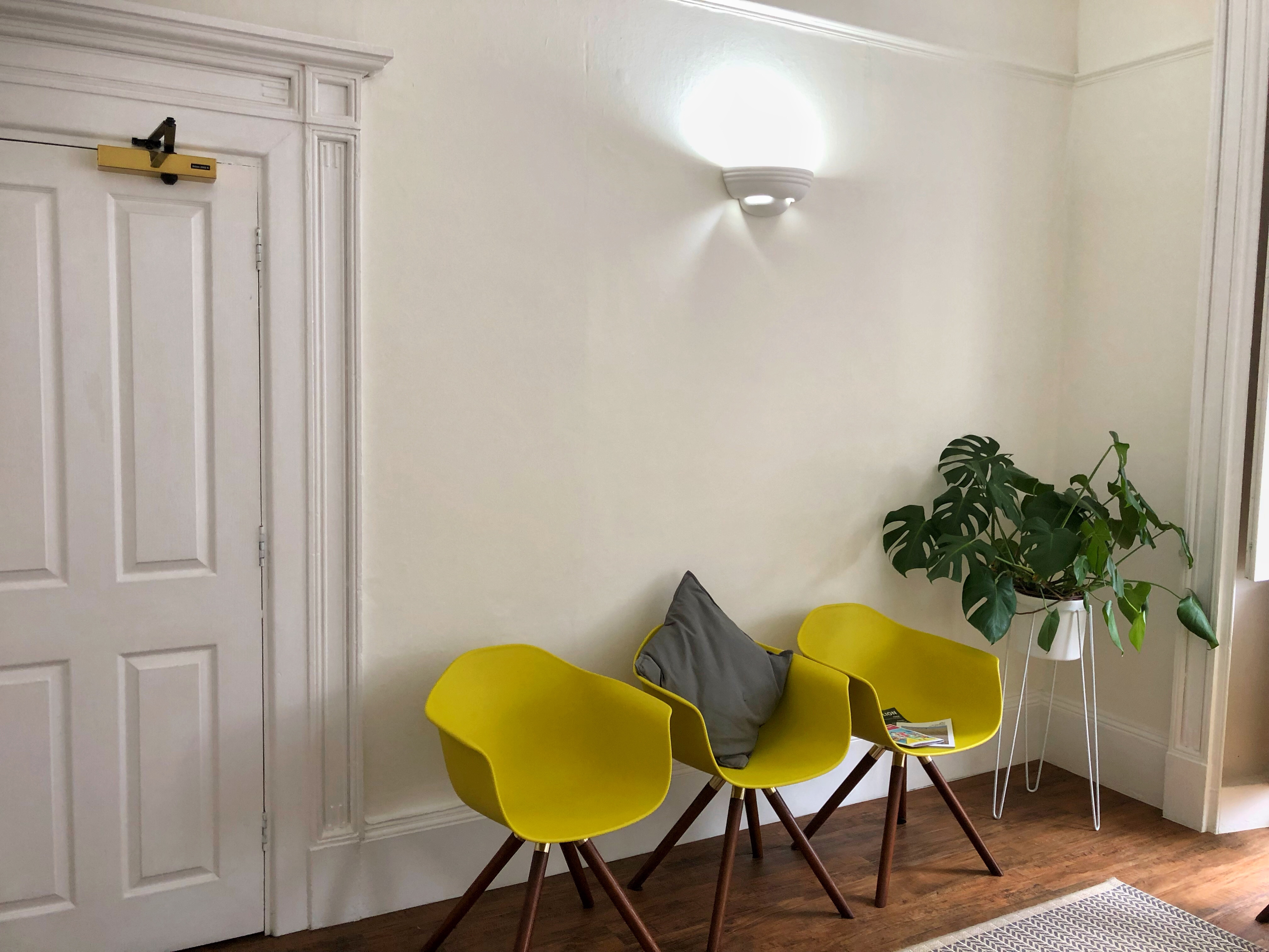 The light and airy waiting room at Move Chiropractic in Cheltenham with seating in the same green/yellow as the logo and a pretty cheese plant on a stand in the corner.