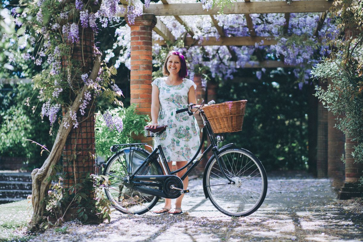 A distance shot of me standing under a wisteria laden veranda holding my pashley bicycle and wearing a pretty floral dress. Part of my headshot photoshoot with Jenny Giles Photography.