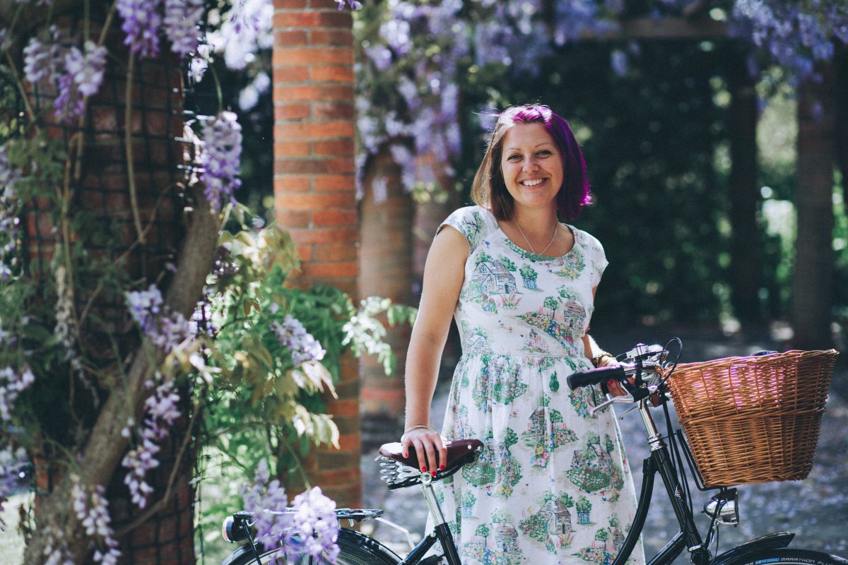 A closer up image of me standing under the wisteria and holding my black pashley bike. From my Jenny Giles Photography headshot photo session.