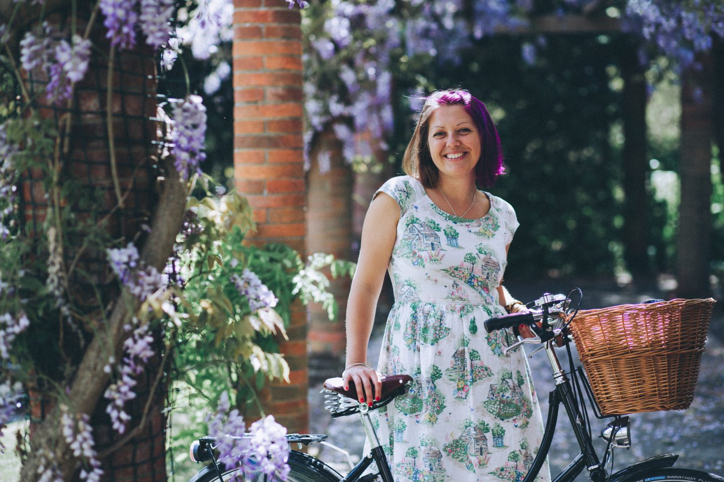 A photo of me standing under some wisteria holding my bike for a post about anxious overwhelm. People often don't believe I suffer from anxiety as I appear so confident. From my Jenny Giles Photography headshot photo session.