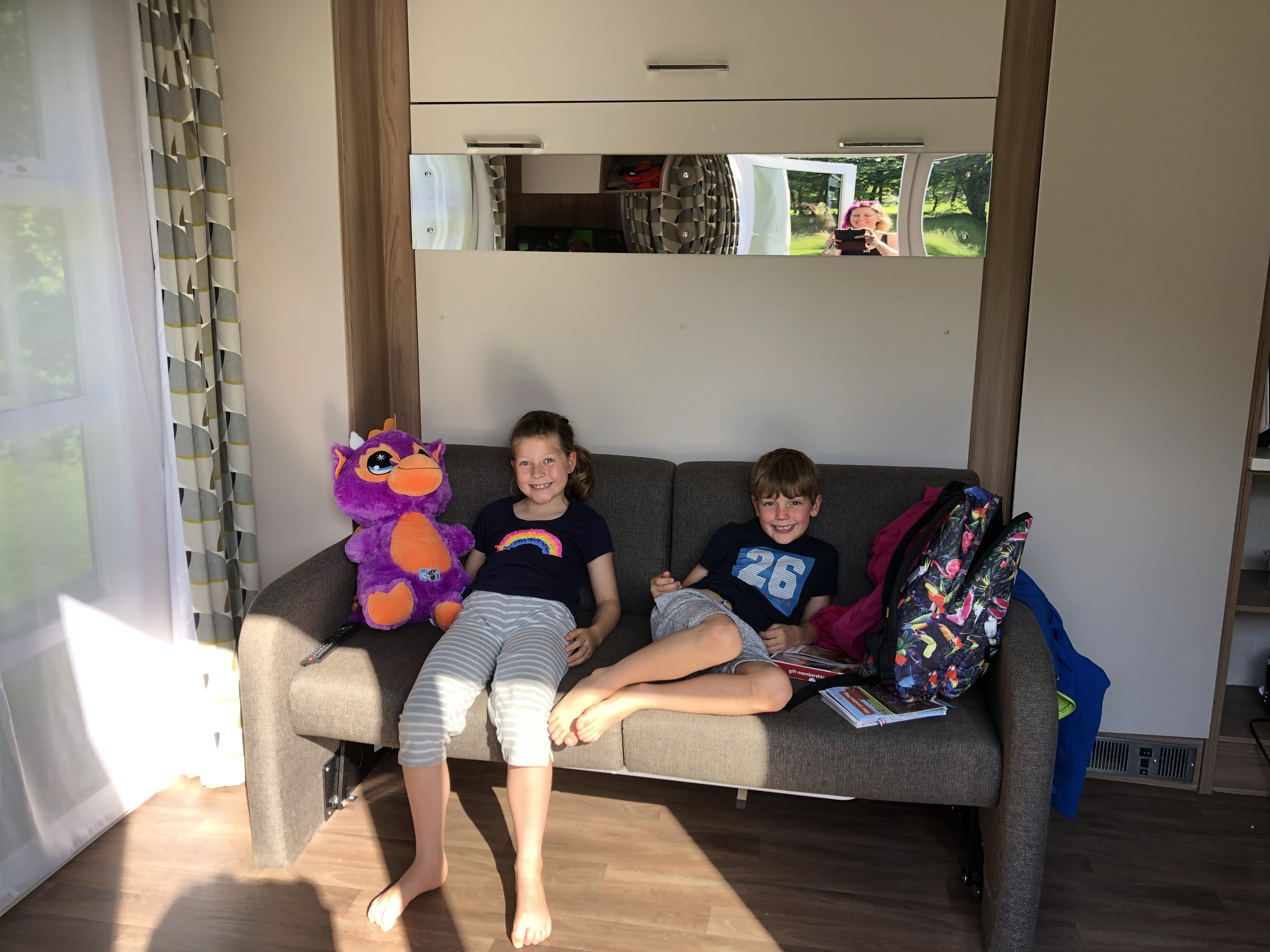 My children sitting on the sofa in the Experience Freedom pod at the Caravan and Motorhome Club site of Alderstead Heath in Surrey.